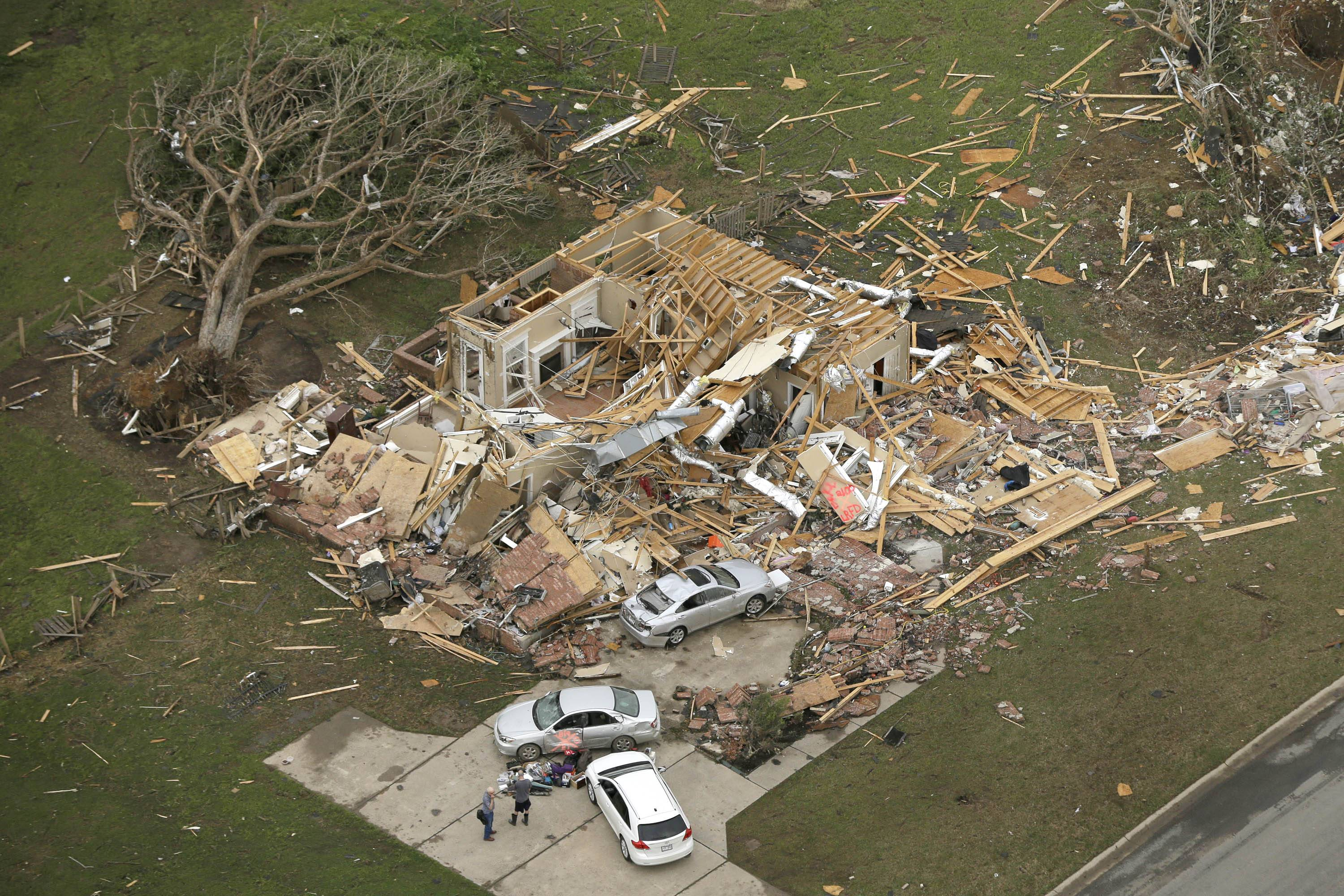 Two men stand in front of a destroyed house in Mayflower, Ark., Monday, April 28, 2014, after a tornado struck the town late Sunday. A tornado system ripped through several states in the central U.S. and left at least 17 dead in a violent start to this year's storm season, officials said.