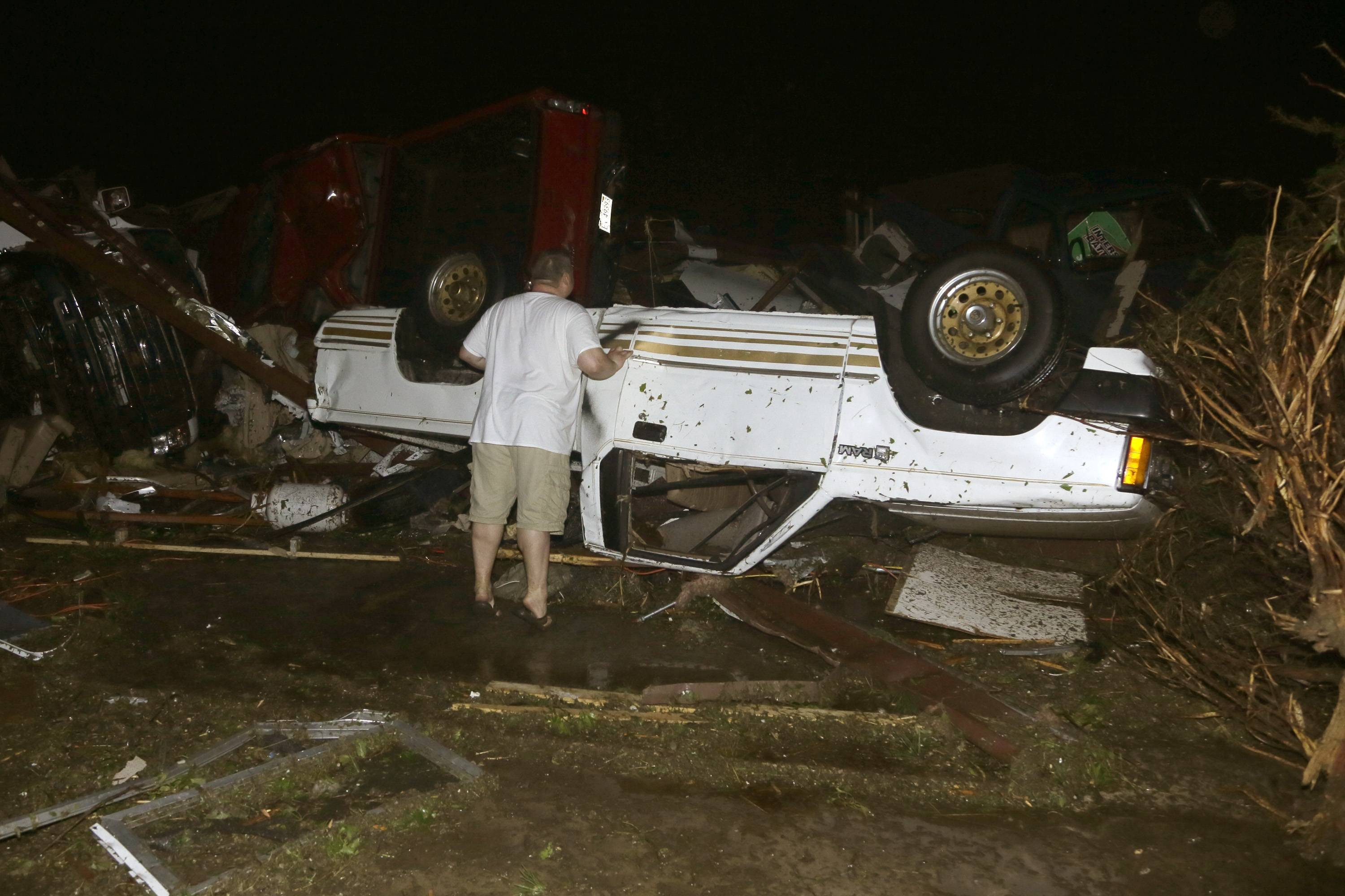 John Ward, an automobile and RV dealer, looks an tornado damage to one of his trucks in Mayflower, Ark., Sunday, April 27, 2014. A tornado struck the dealer's on lot Sunday.