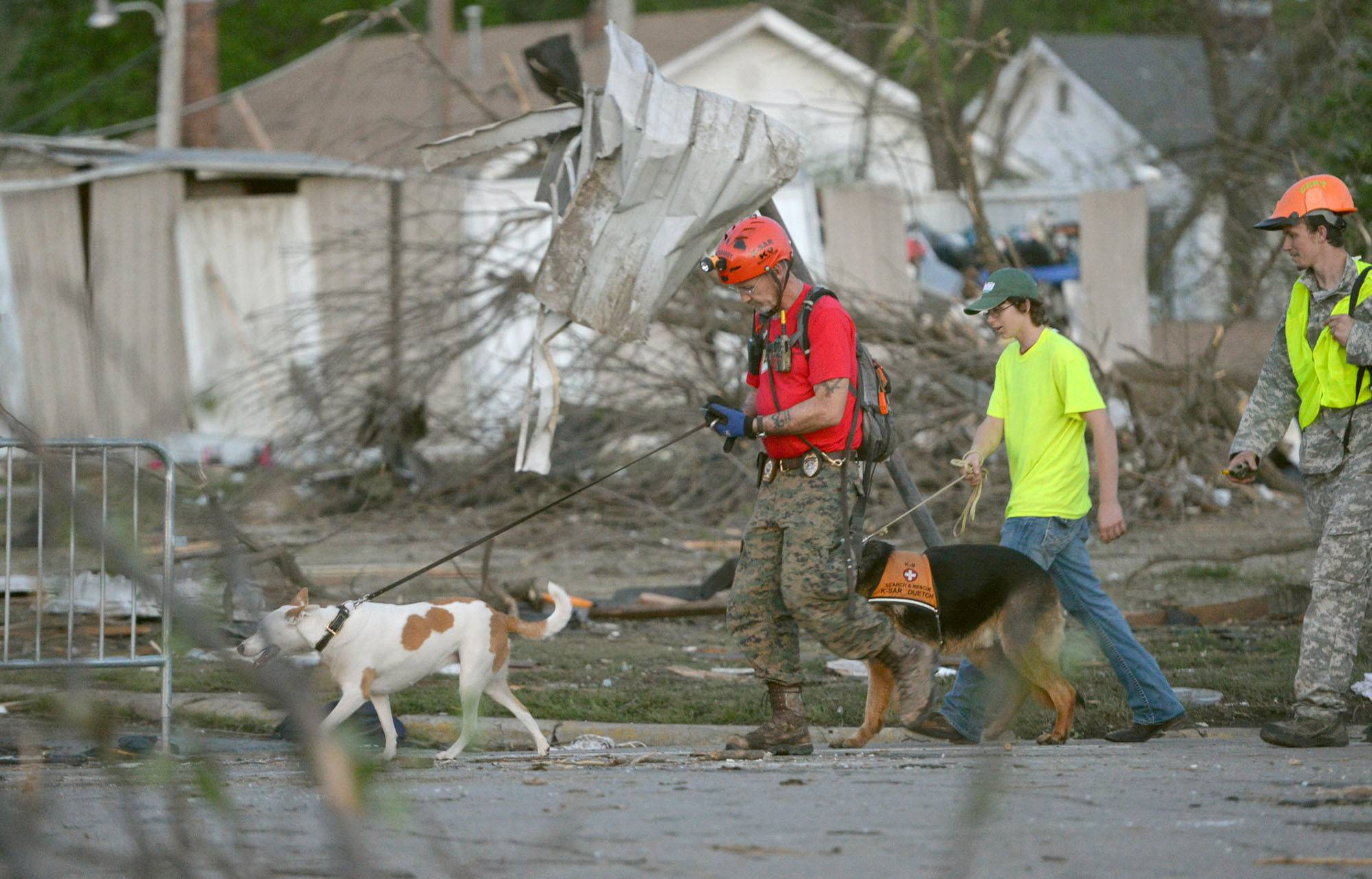 A K-9 rescue unit walks along Military Street in Baxter Springs, Kan., April 27, 2014, as they survey the damage from Sunday's tornado. A powerful storm system rumbled through the central and southern United States on Sunday, spawning a massive tornado that carved through Little Rock's northern suburbs and another that hit Oklahoma and Kansas.