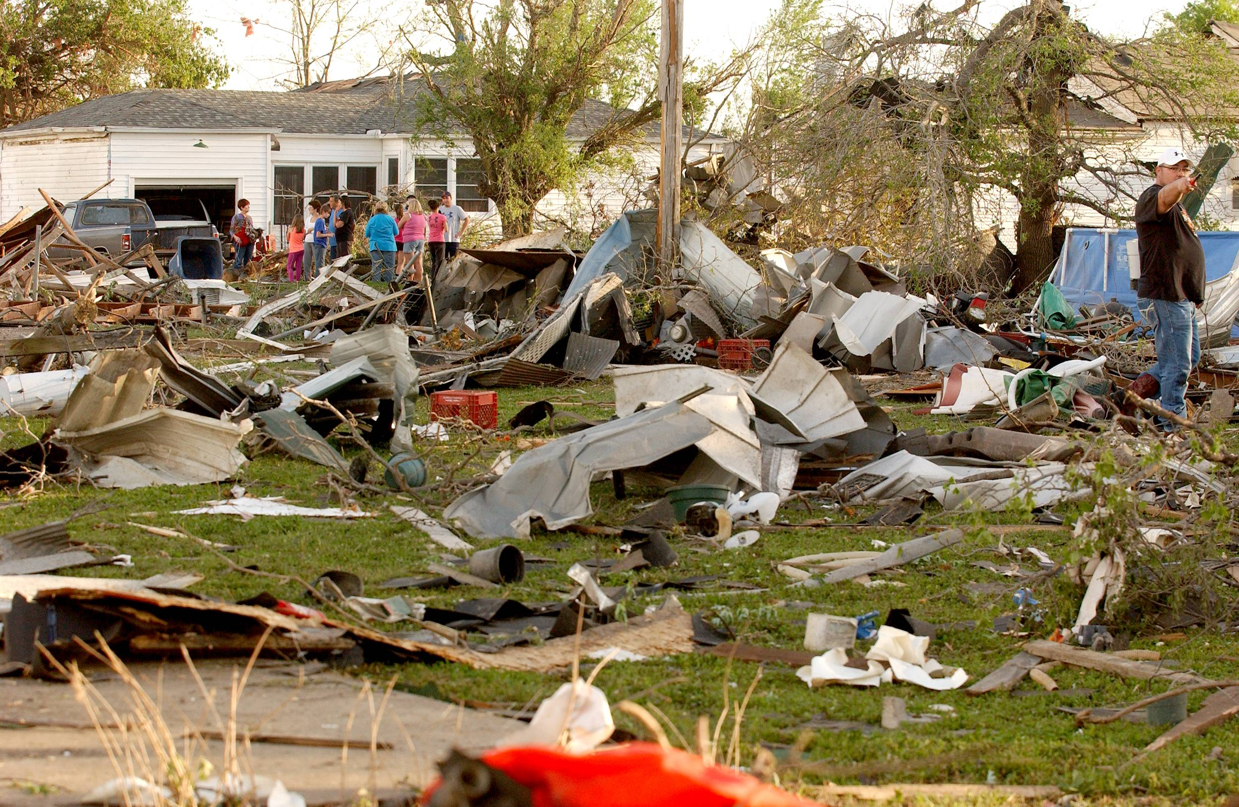 Quapaw, Okla., residents survey the damage in a residential neighborhood struck by a tornado on Sunday evening, April 27, 2014. A powerful storm system rumbled through the central and southern United States on Sunday, spawning a massive tornado that carved path of destruction through the northern Little Rock suburbs and another twister that killed two people in Oklahoma and injured others in Kansas.