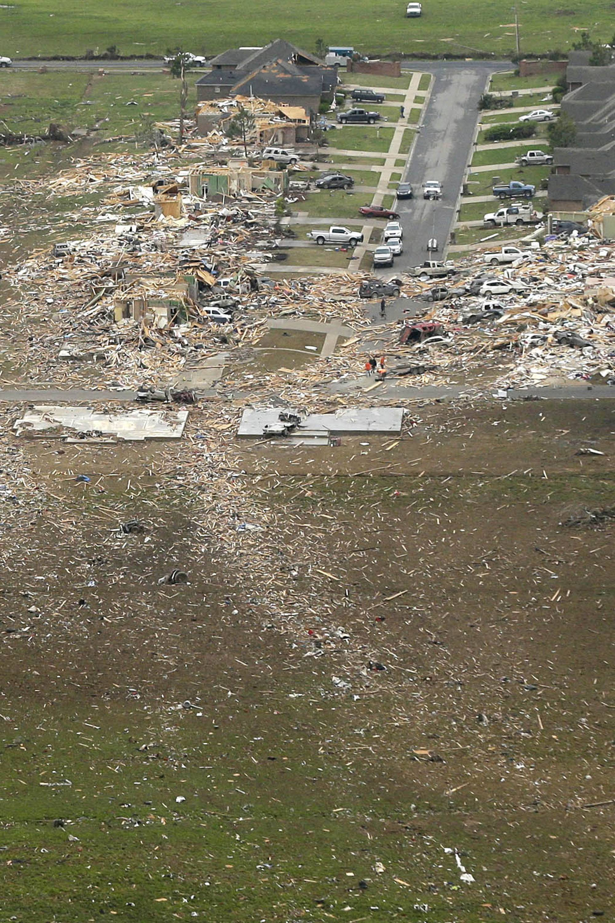 A trail of debris, bottom, leads along the path of a tornado-devastated neighborhood in Vilonia, Ark., Monday, April 28, 2014, after a tornado struck the town late Sunday. The most powerful twister this year carved an 80-mile path of destruction through suburbs north of the state capital of Little Rock, killing at least 16 people.