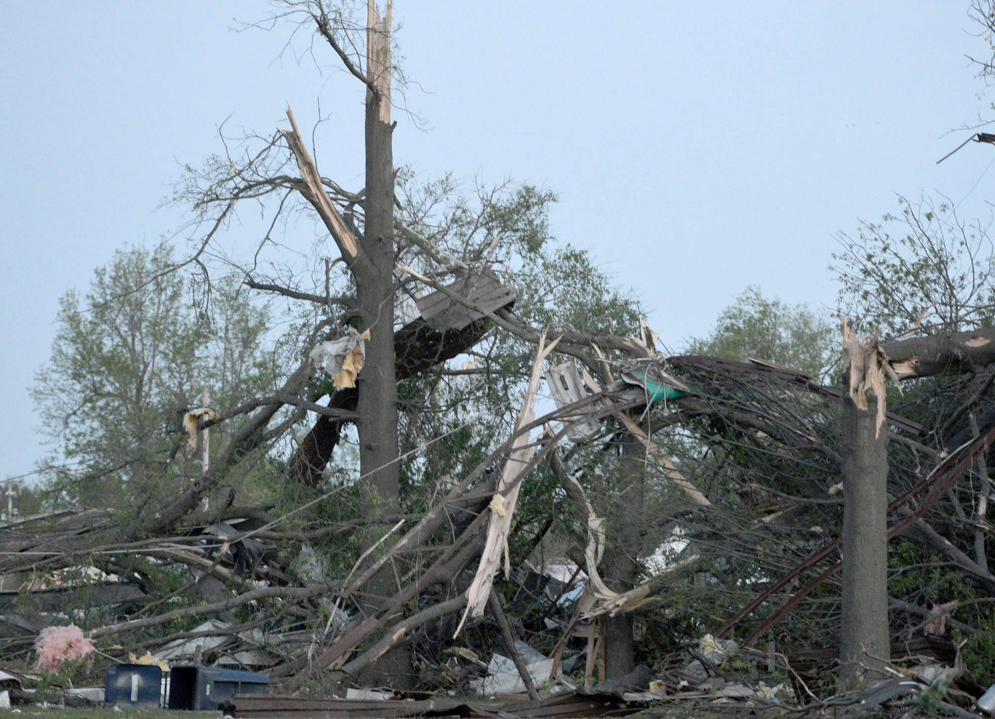 Twisted trees and power lines remain in a residential block near Military Avenue following the tornado in Baxter Springs, Kan., Sunday, April 27, 2014. A powerful storm system rumbled through the central and southern United States on Sunday, spawning a massive tornado that carved through Little Rock's northern suburbs and another that hit Oklahoma and Kansas.