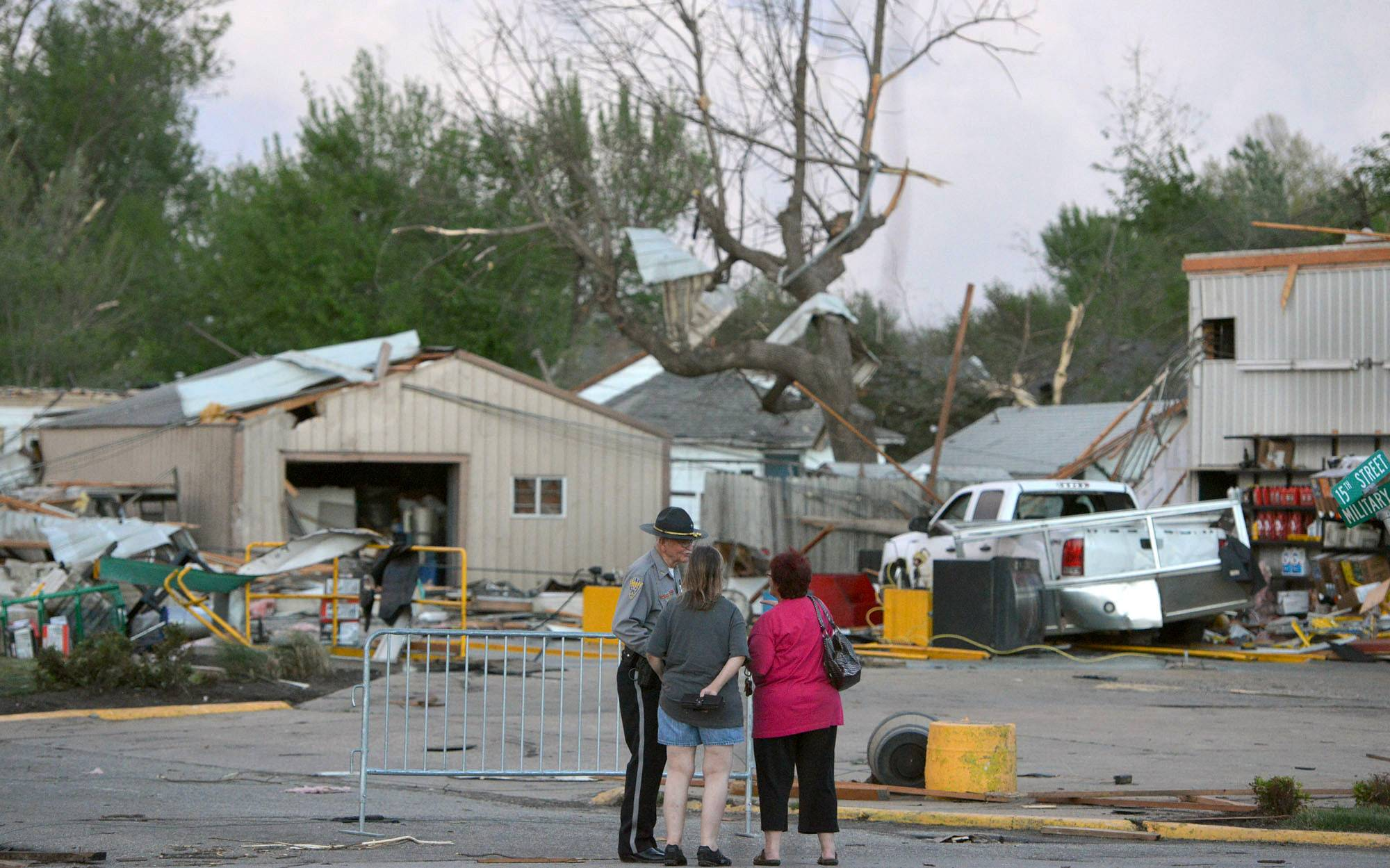 A officer talks to people at 15th and Military following Sunday's tornado in Baxter Springs, Kan., Sunday April 27, 2014. A powerful storm system rumbled through the central and southern United States on Sunday, spawning a massive tornado that carved through Little Rock's northern suburbs and another that hit Oklahoma and Kansas.