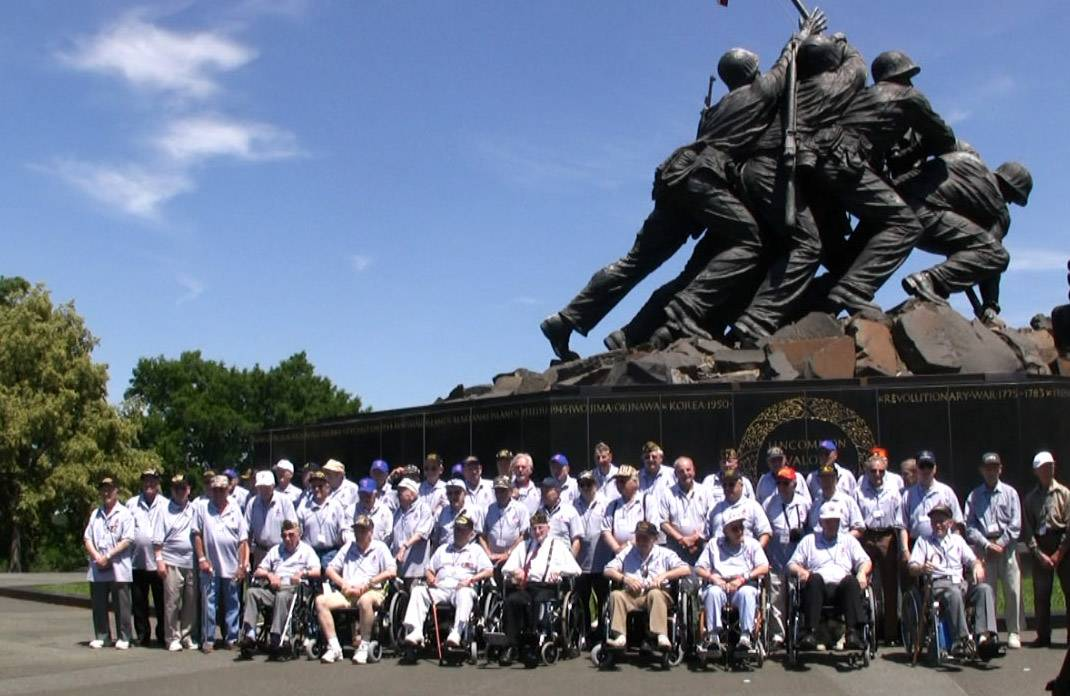 Veterans on Honor Flight trips visit the memorials for their branch of the military. Here, veterans from the Chicago area get a group photo at the U.S. Marine Corps War Memorial.