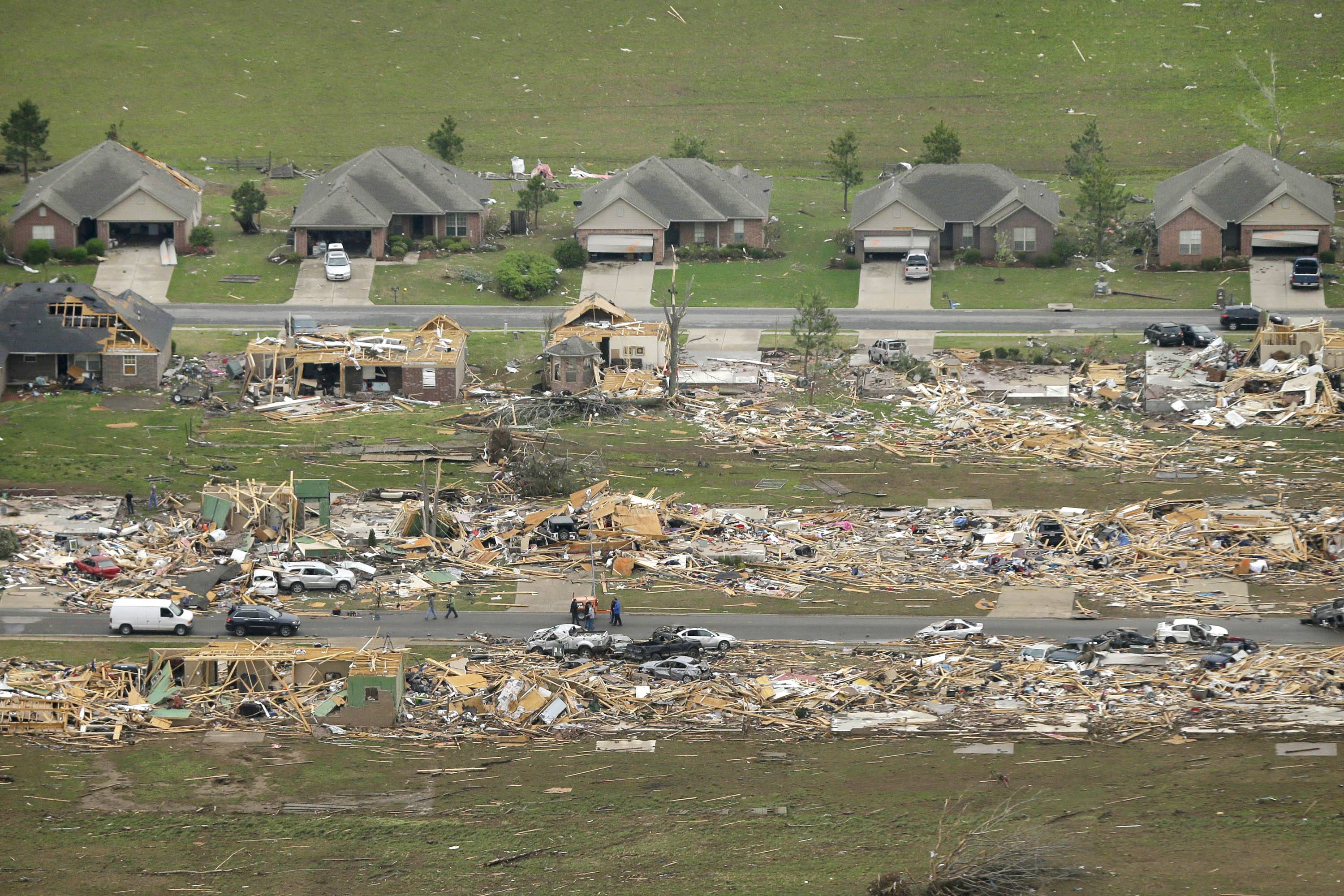 A row of lightly damages houses, top, face destroyed homes in a Vilonia, Ark., neighborhood Monday, after a tornado struck the town late Sunday, killing at least 16 people.