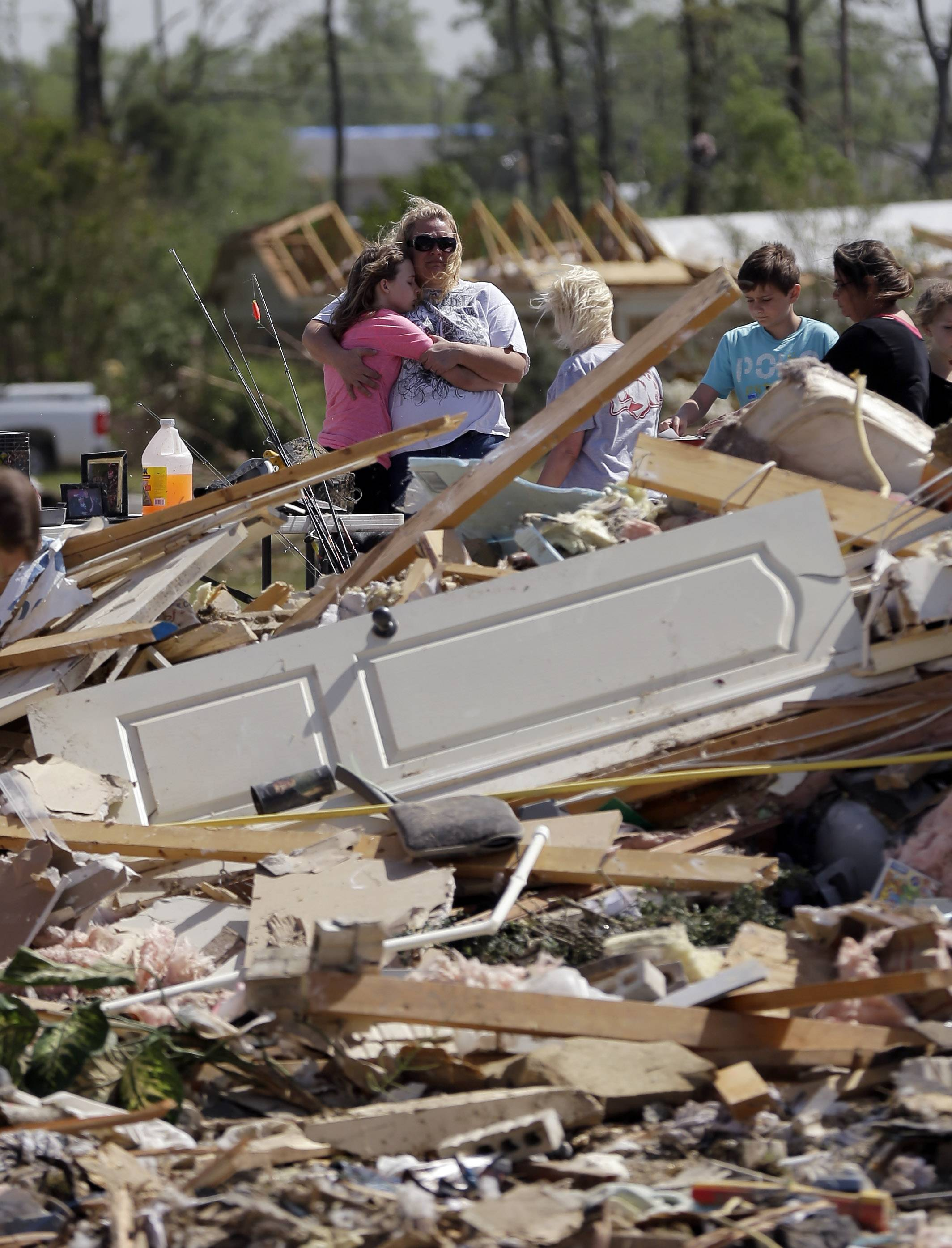 Residents and friends sift through debris Monday, a day after a tornado struck Vilonia, Ark.