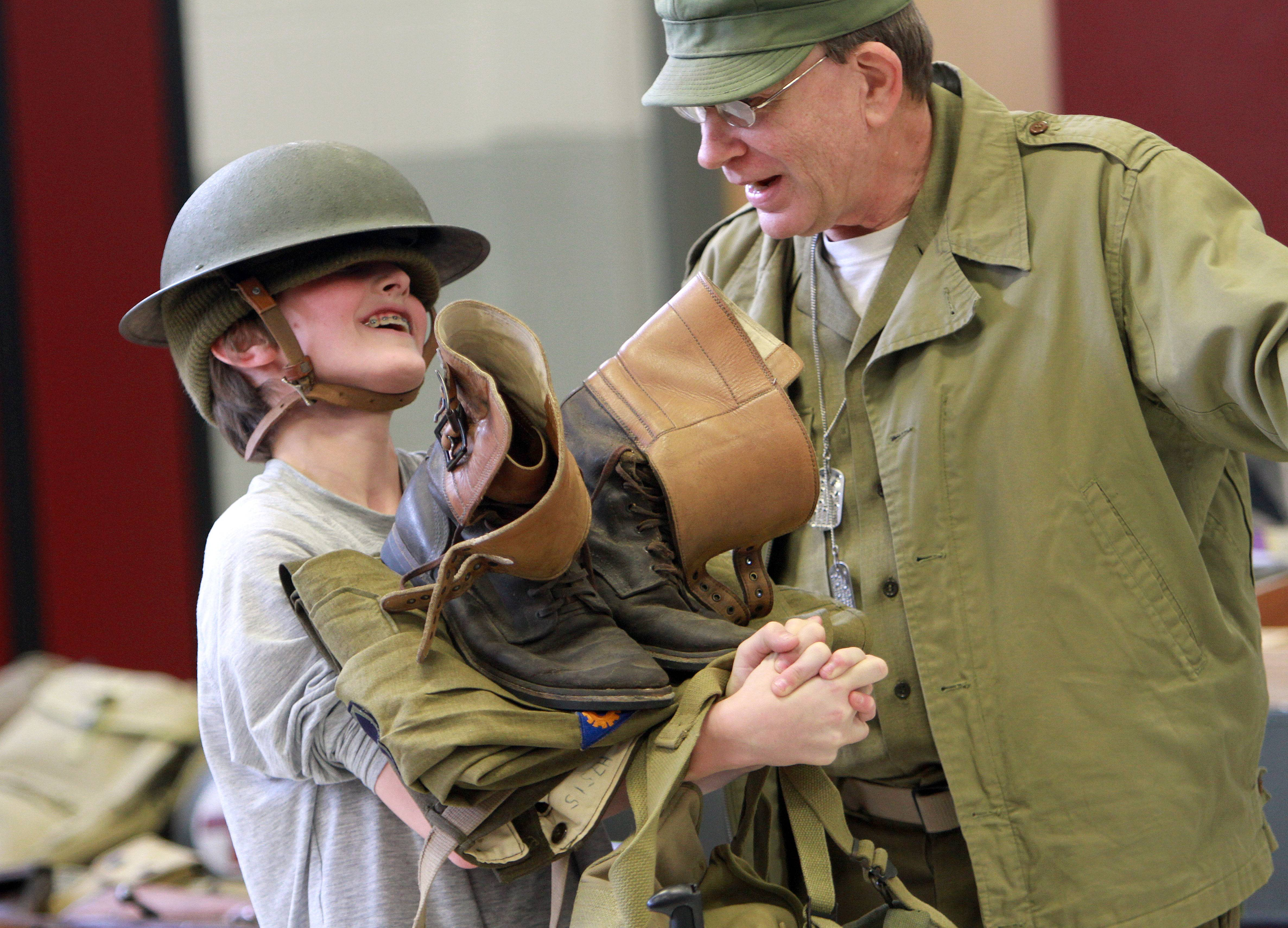 Eighth grader Hunter Lasky is loaded down with an army uniform by WWII reenactor Phil Lauricella, of Elburn, Thursday at Fremont Middle School in Mundelein.