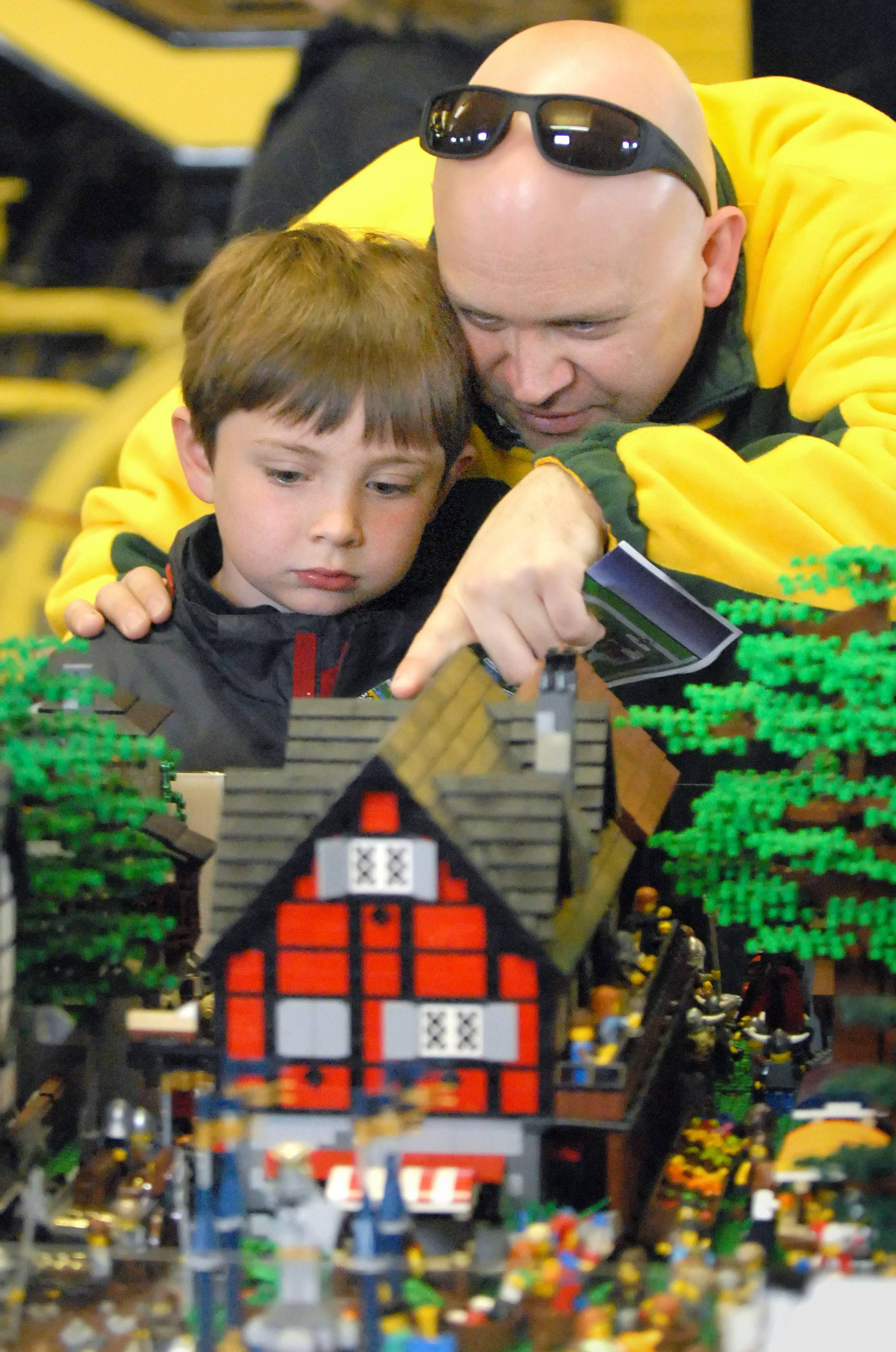 "Steve Drews, of North Aurora, points out details to his son, Philip, 6, of the medieval city created by Dale Klein, of Hickory Hills, on display at Blackberry Farm's LEGO Bash event in Aurora on Sunday. Both are LEGO fans and Steve says seeing the LEGO displays is like taking a ""trip back to childhood."" Members of the Northern Illinois LEGO Train Club set up displays at the farm over the weekend."