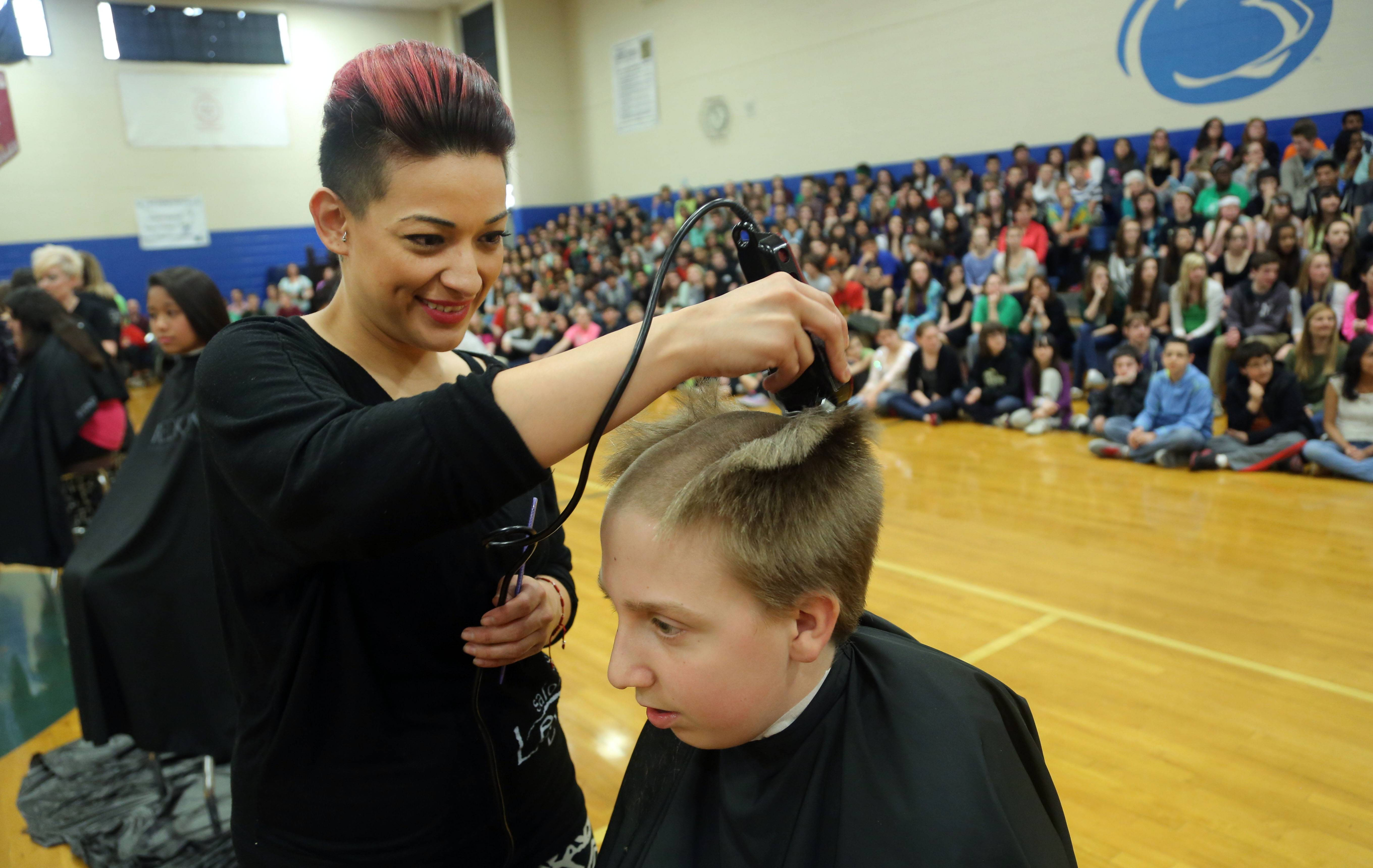 Crystal Sepulveda of Legacy salon.spa shaves the head of 13-year-old Griffin Hayes during a St. Baldrick's assembly at Grayslake Middle School Thursday.