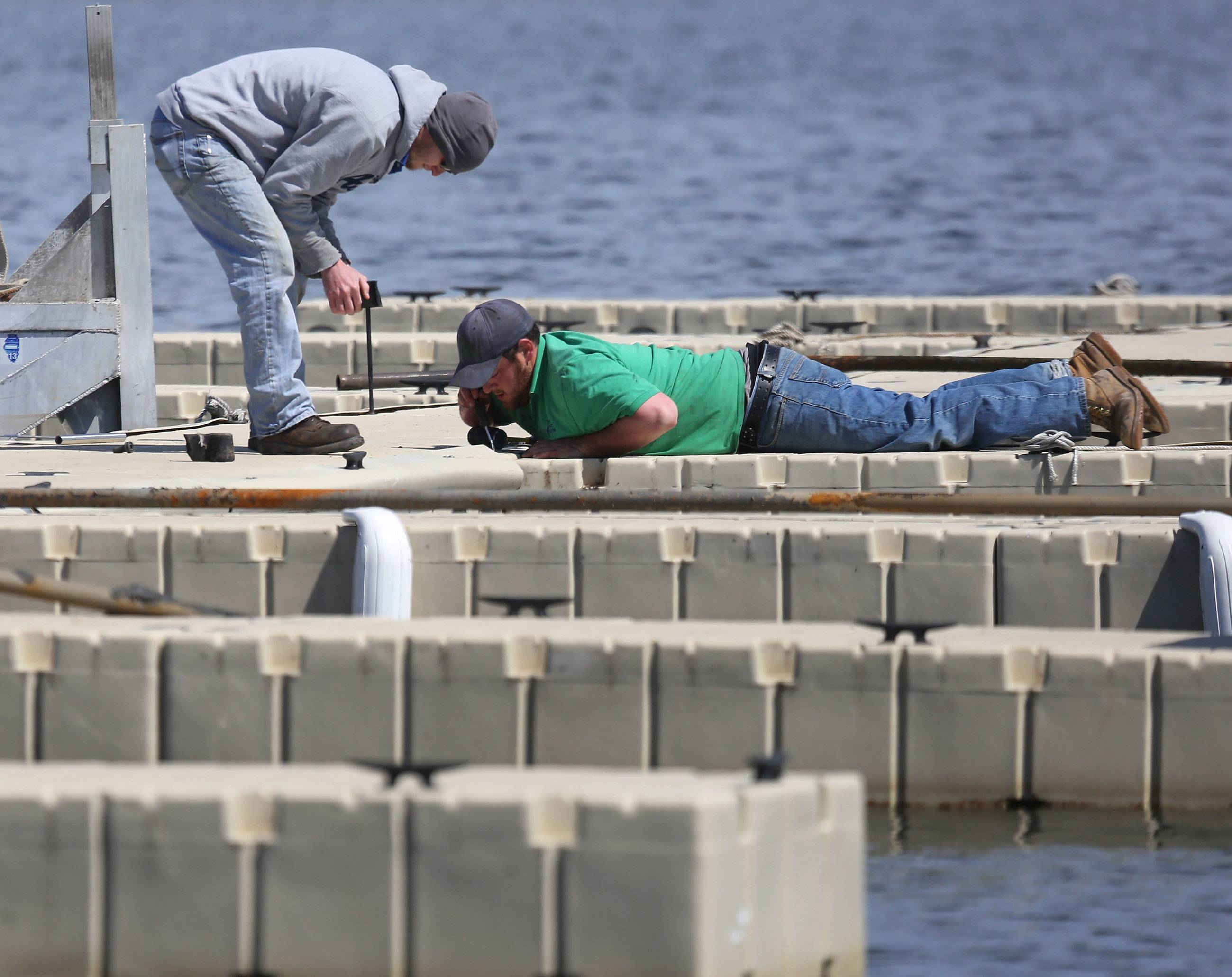 Technicians Alex Ellis, left, and Jake Forni, of Rollins Aquatics, repair the piers and docks at Lindy's Landing on Bangs Lake in Wauconda Wednesday. The extremely cold winter caused the docks to be in worse shape than in previous years.