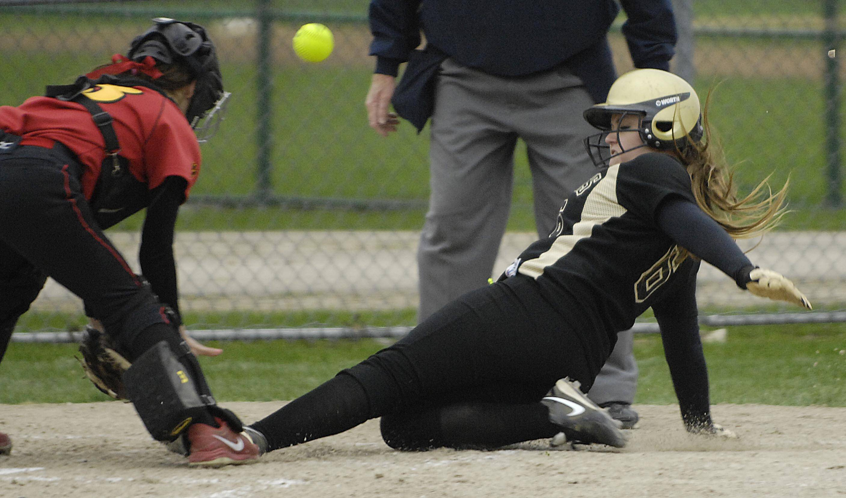 Streamwood's Melissa Malcolm scores the first run of the second inning on an outfield hit by teammate Mercedes Olmos as the ball bounces away from Batavia catcher Christina Karius Monday in Batavia.