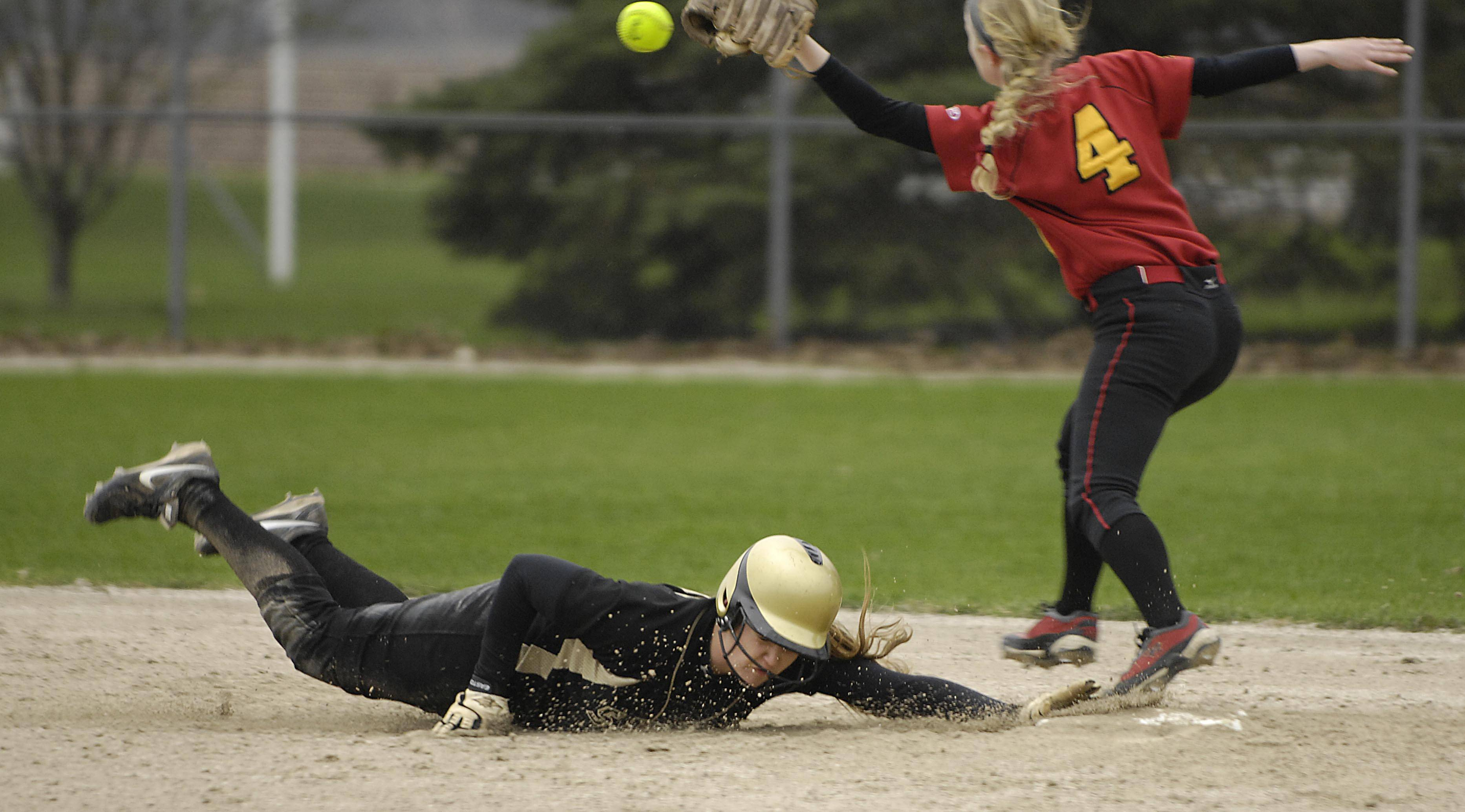 Streamwood's Melissa Malcolm dives safely back to second base as the throw from the outfield gets away from Batavia second baseman Elyse Burns in the fifth inning Monday in Batavia. Malcolm scored later in the inning to put her team up 6-3.