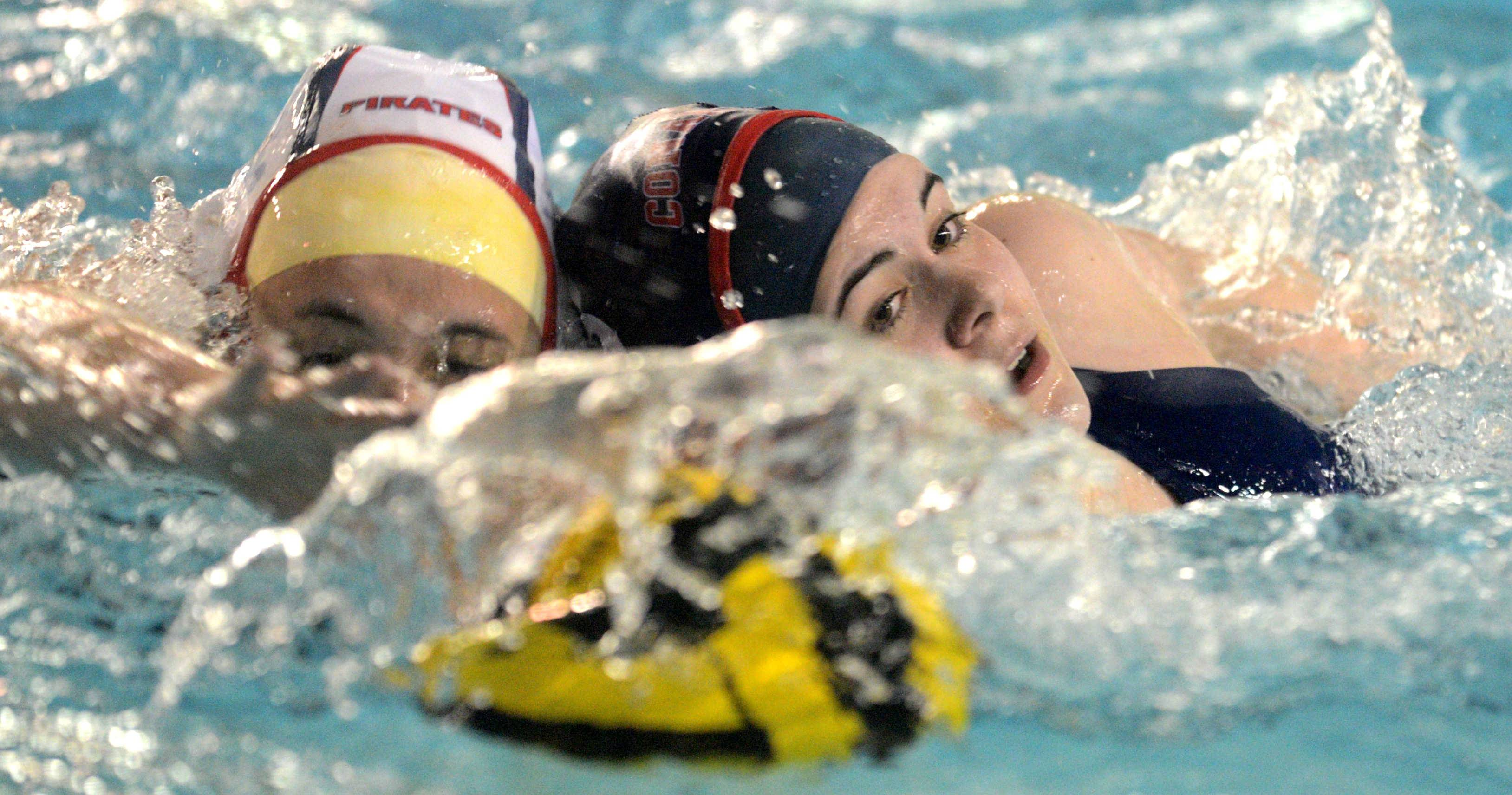 Conant's Claire Rosas, right, races Palatine's Emily Seidl to the ball during a varsity water polo match at Conant on Monday night.