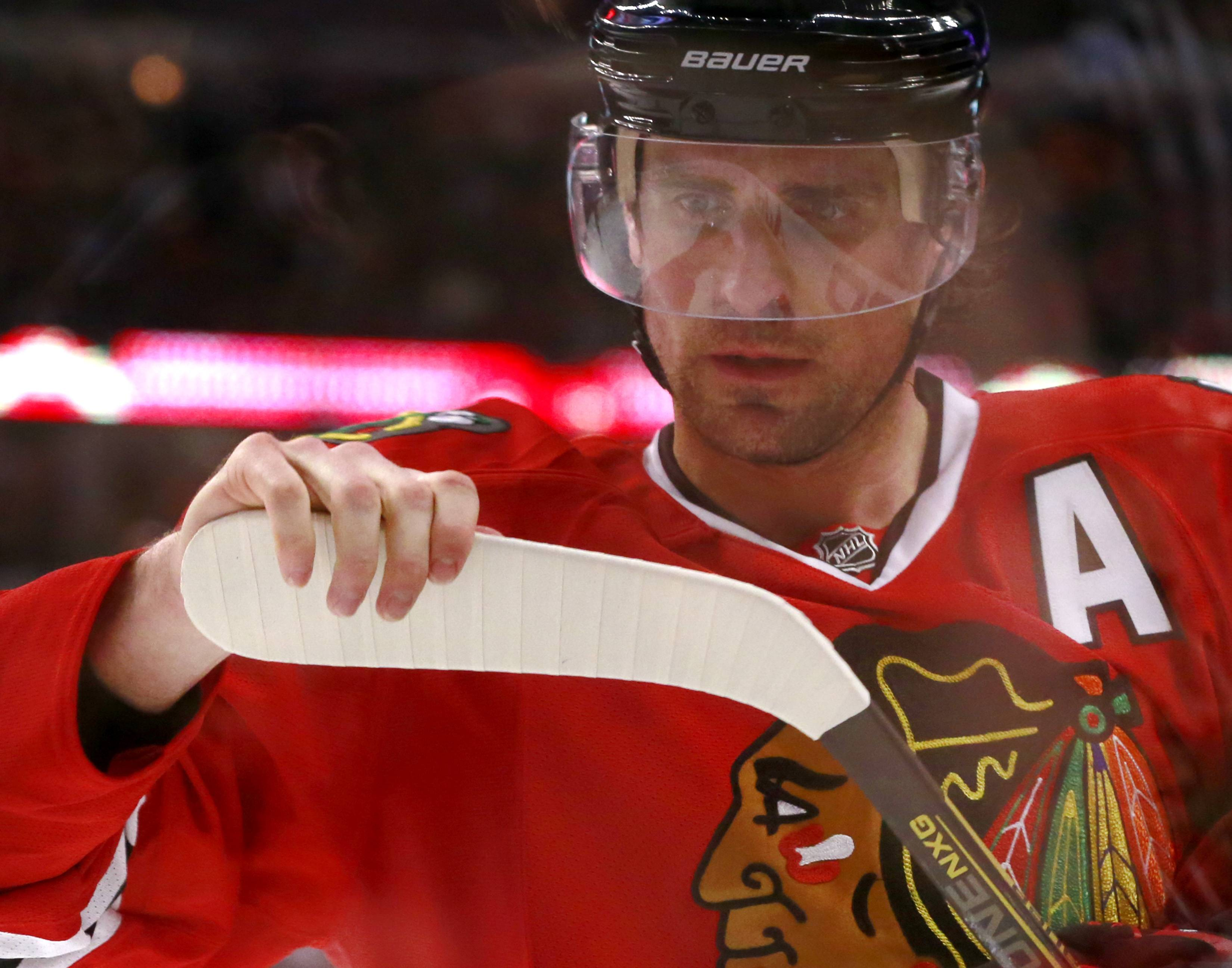 Blackhawks wing Patrick Sharp checks the blade of his stick during a break in play during the first round.