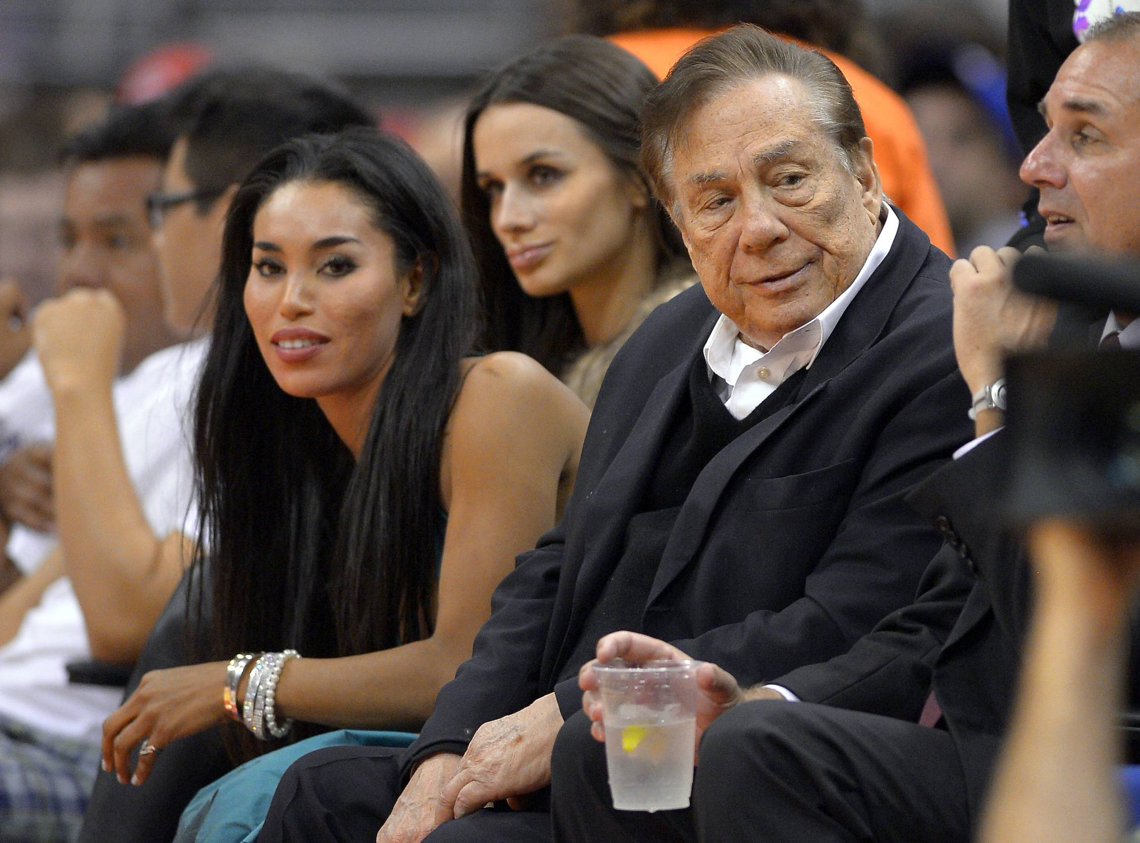 Los Angeles Clippers owner Donald Sterling, right, and V. Stiviano, left, watch the Clippers play the Sacramento Kings during the first half of an NBA basketball game in Los Angeles on Oct. 25, 2013.