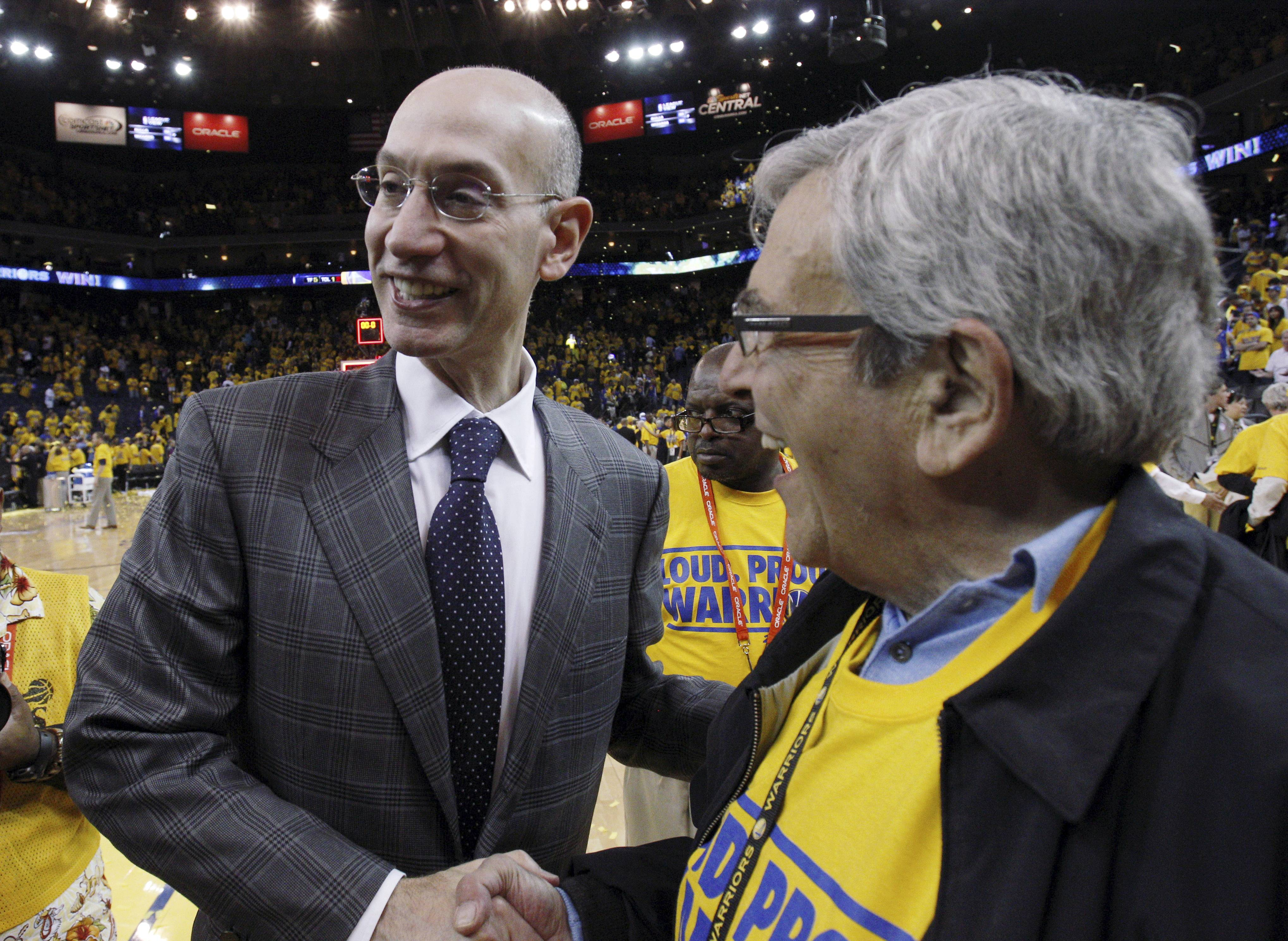 NBA commissioner Adam Silver, left, shakes hands with a fan after Game 4 of an opening-round NBA basketball playoff series between the Golden State Warriors and Los Angeles Clippers on Sunday in Oakland, Calif.