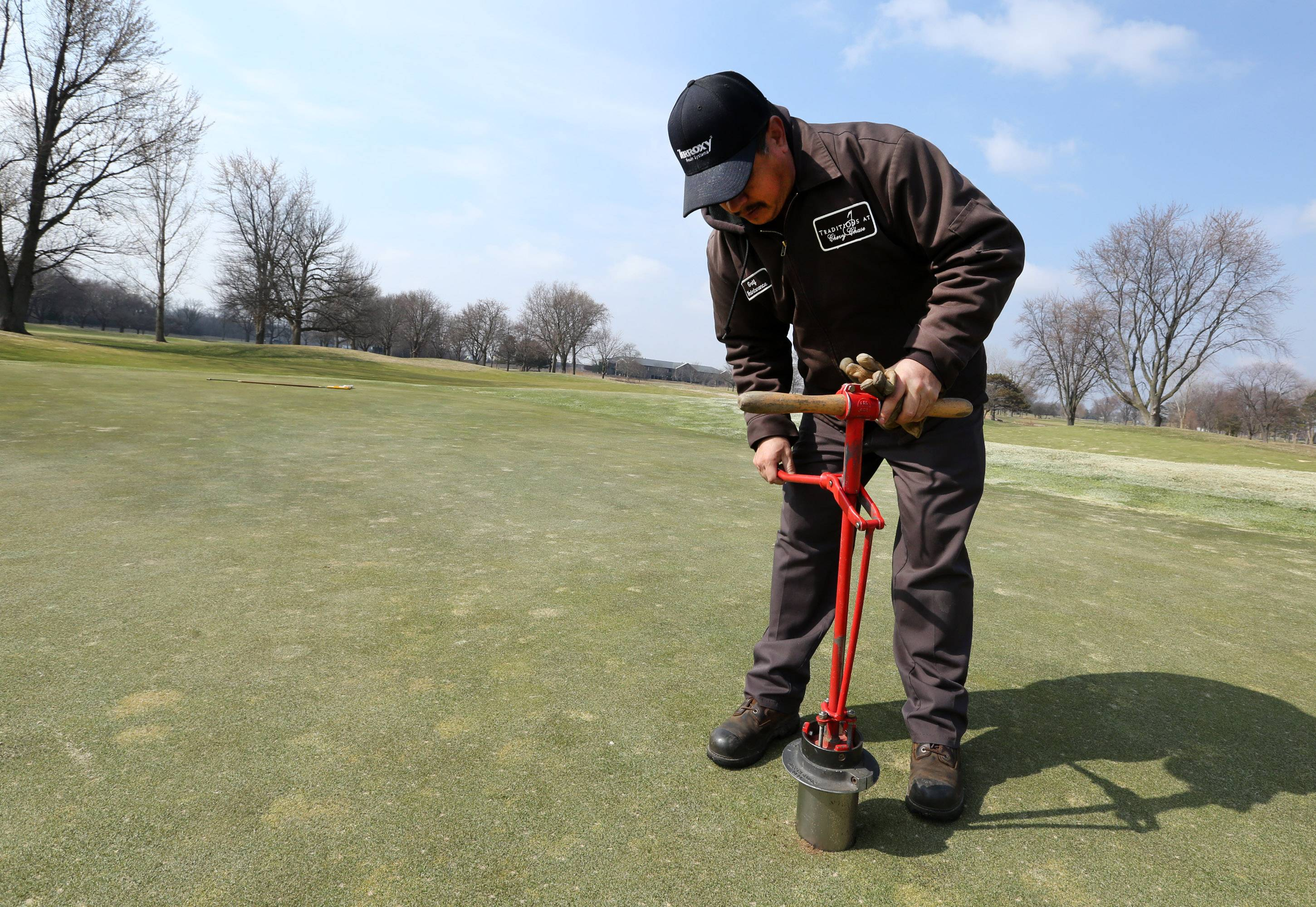 George LeClaire/gleclaire@dailyherald.comAlejandro Mata, greens keeper, setting pins at Chevy Chase Golf Course on Tuesday in Wheeling.