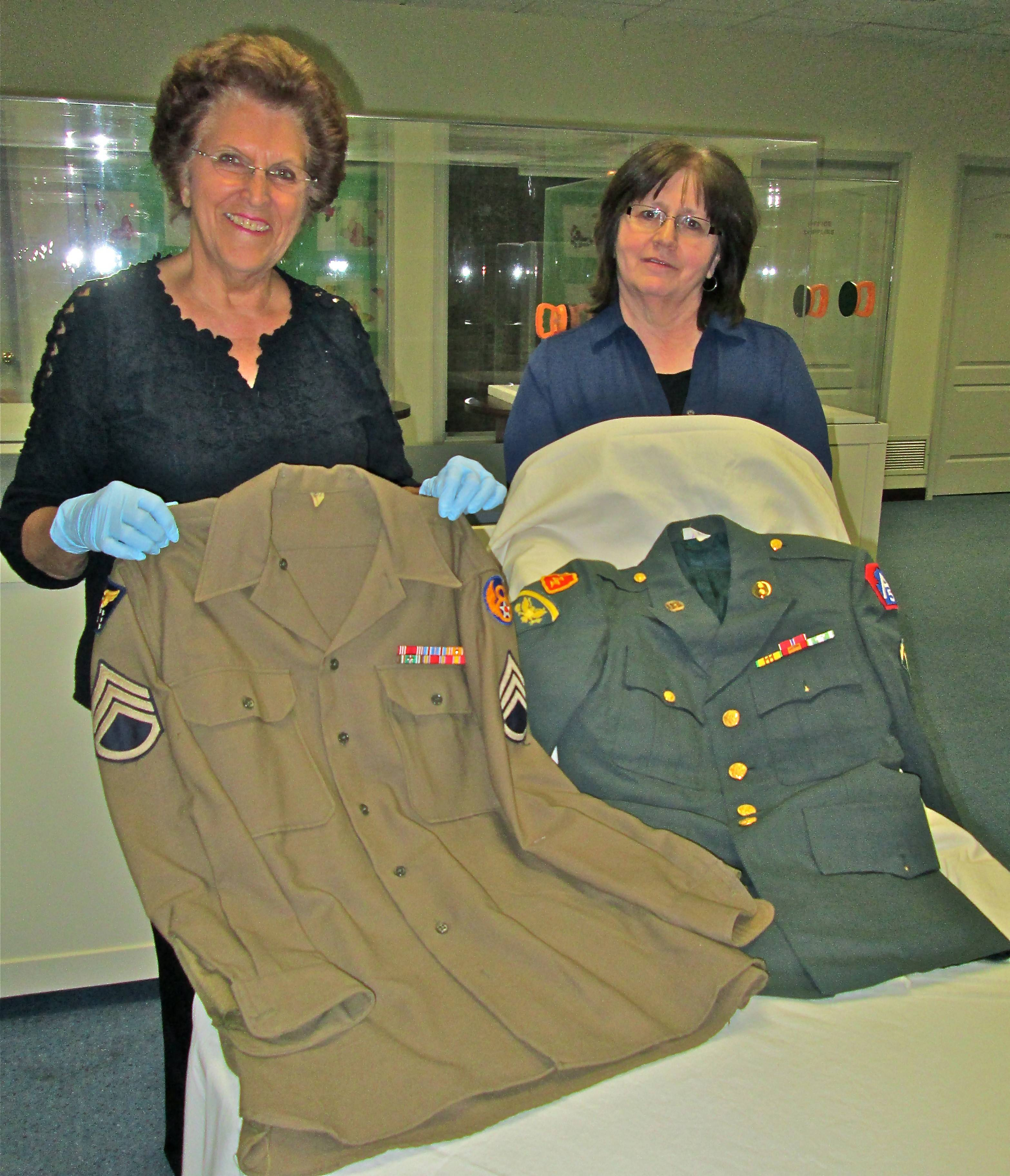 Glen Ellyn Historical Society's past president and curator, Ruth Wright, left, and Executive Director Jan Shupert-Arick prepare the Becker family's donation of military uniforms for exhibit on Memorial Day.