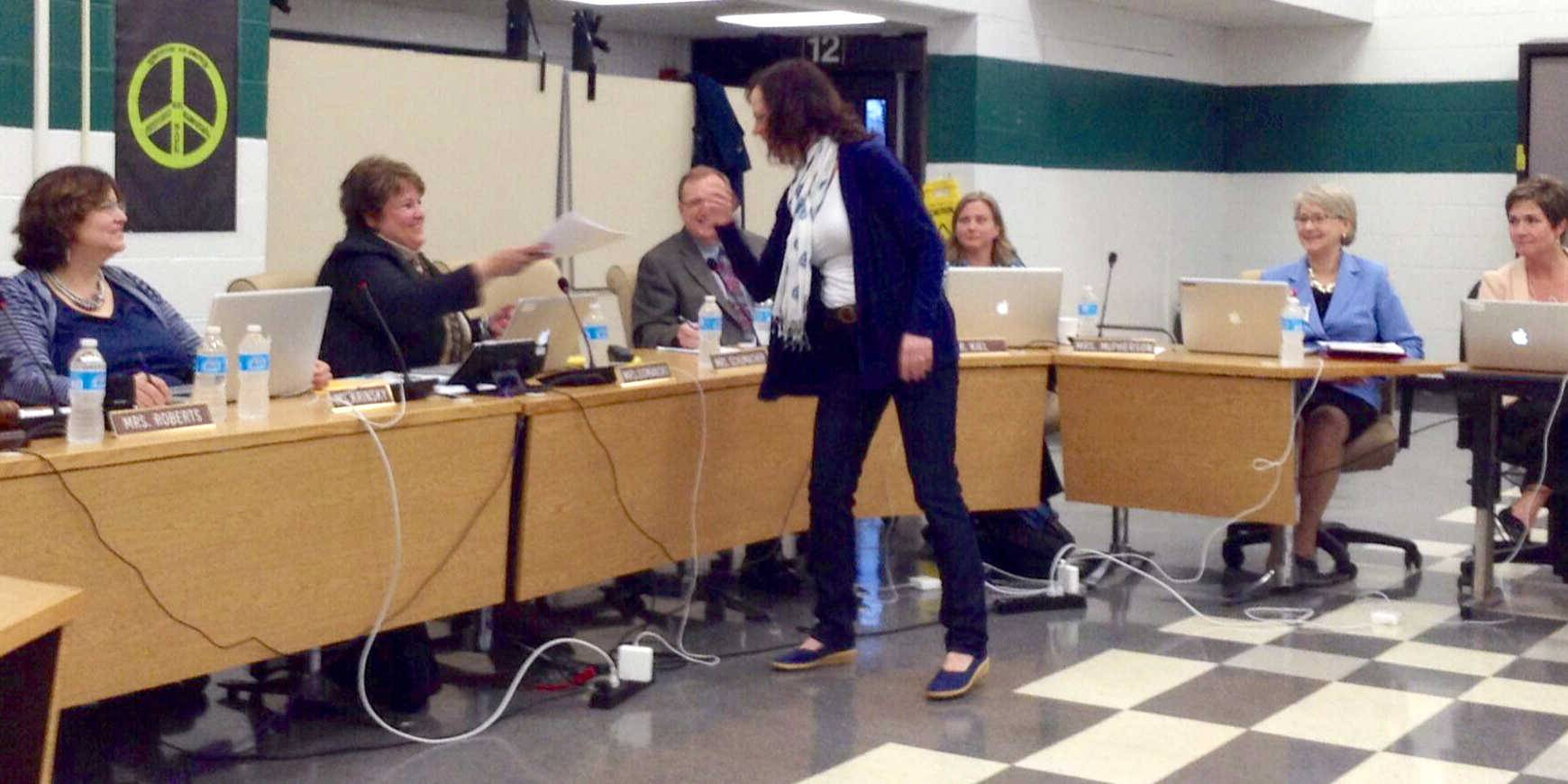 Elizabeth Galliano, a parent whose children attend the Ridge Family Center for Learning, presents a petition to the District 59 school board Monday night that was signed by some 90 parents who are opposed to plans to shorten the Ridge class day.