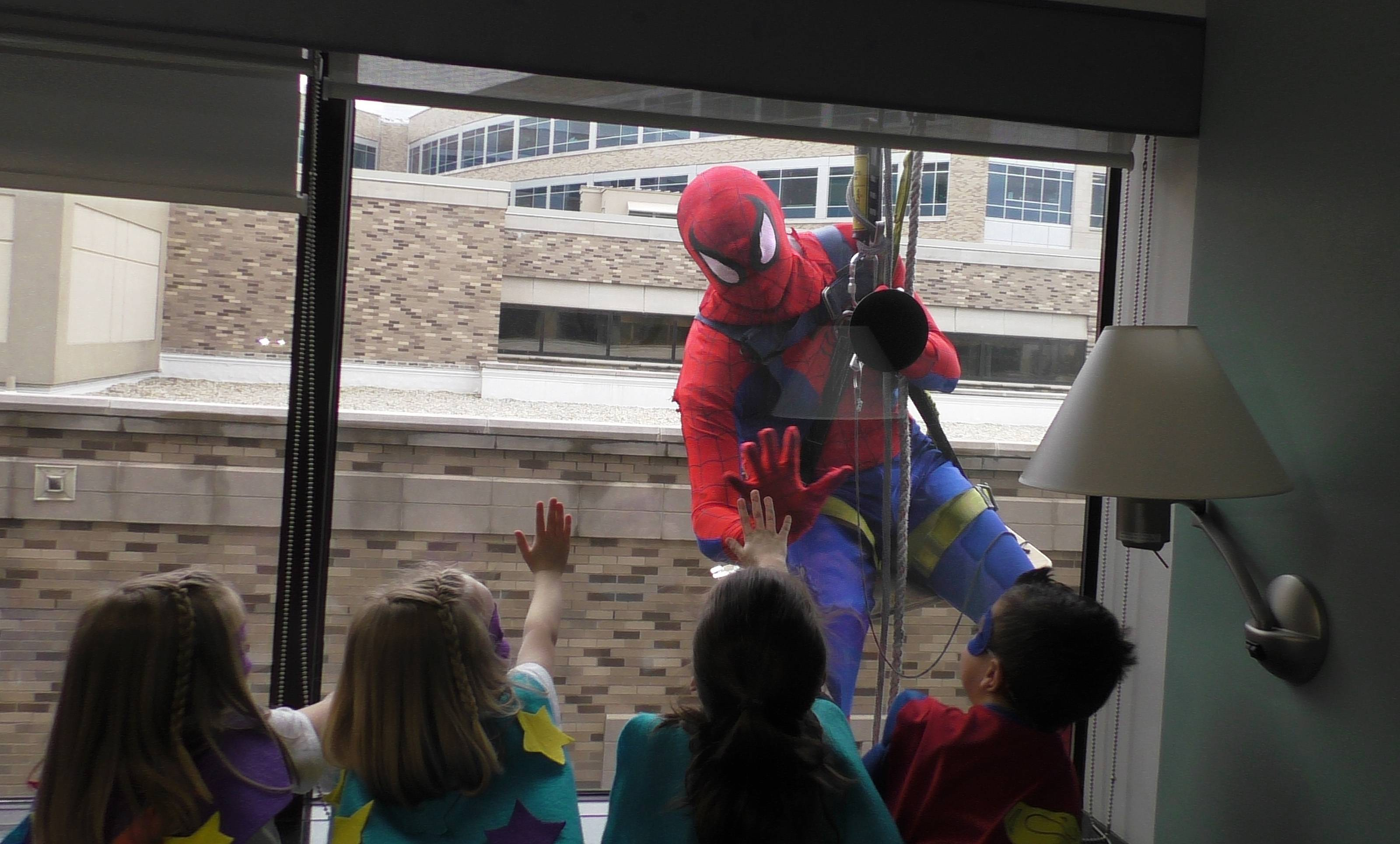 Patients in Central DuPage Hospital's pediatric unit participated in a National Superhero Day event Monday, complete with handmade capes, mask decorations and window washers dressed as superheroes.