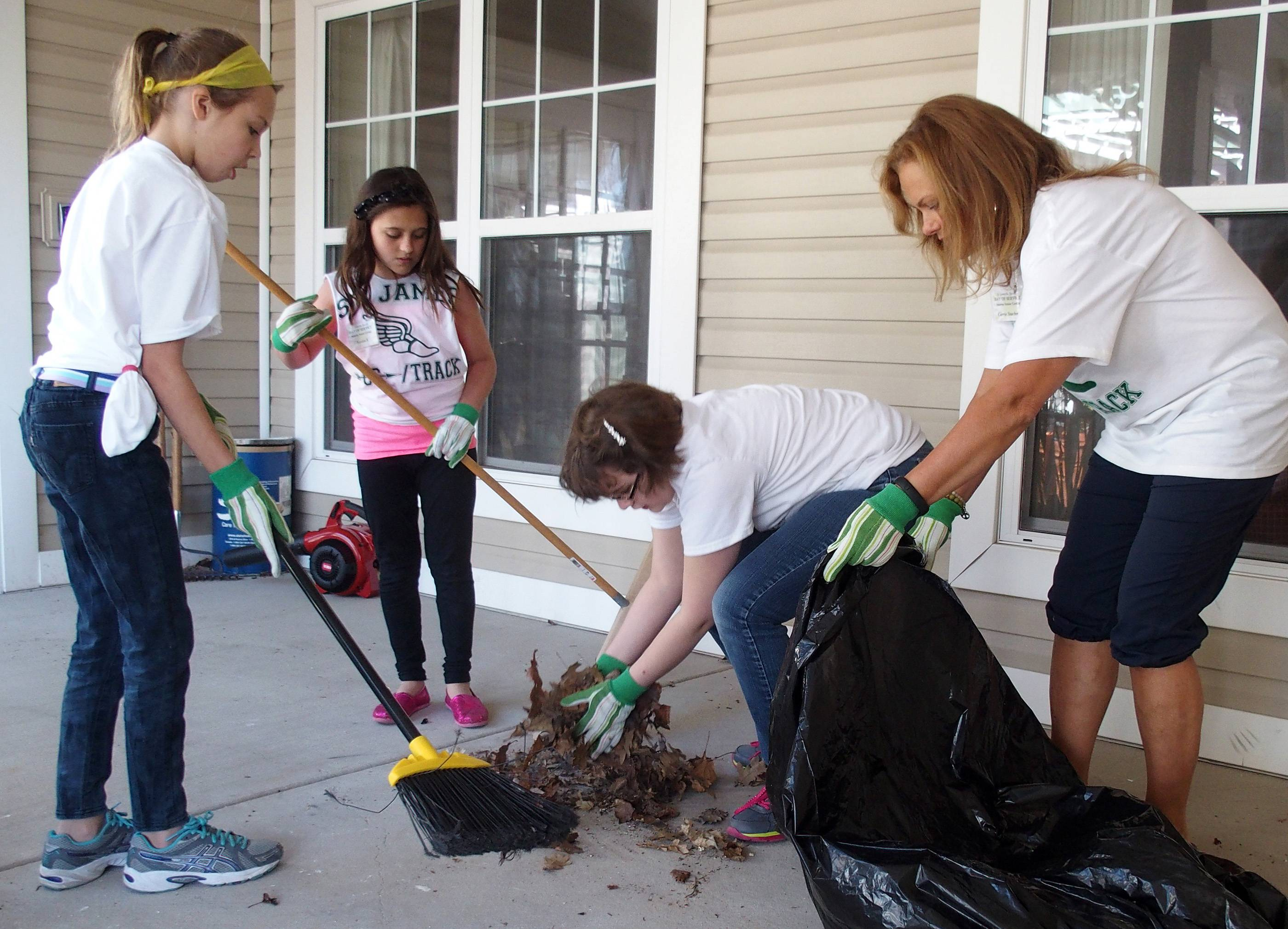 Students from Glen Ellyn's St. James the Apostle School recently participated in a Day of Service project in which they tackled grade-appropriate activities at their school and 16 locations across Glen Ellyn. Some students, including Emma Nielsen, Sophia Stachnik and Gillian Weesner, joined volunteer mom Carrie Stachnik, right, in cleaning up the porch at Sunrise Senior Living Center and Brighton Gardens.