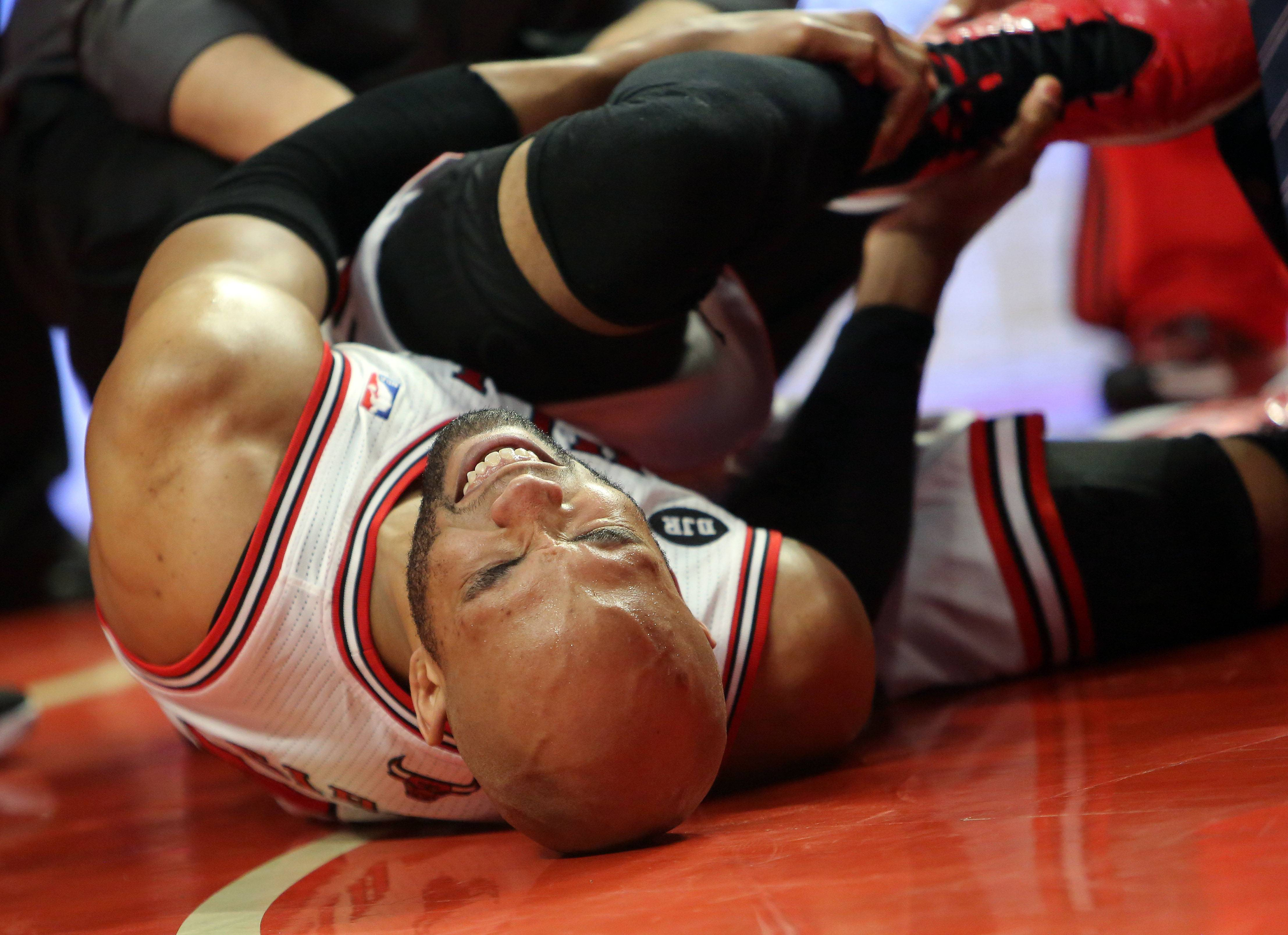 Chicago Bulls forward Taj Gibson holds his ankle during the Bulls 75-69 loss in game five of first-round of the NBA playoffs Tuesday night at the United Center.