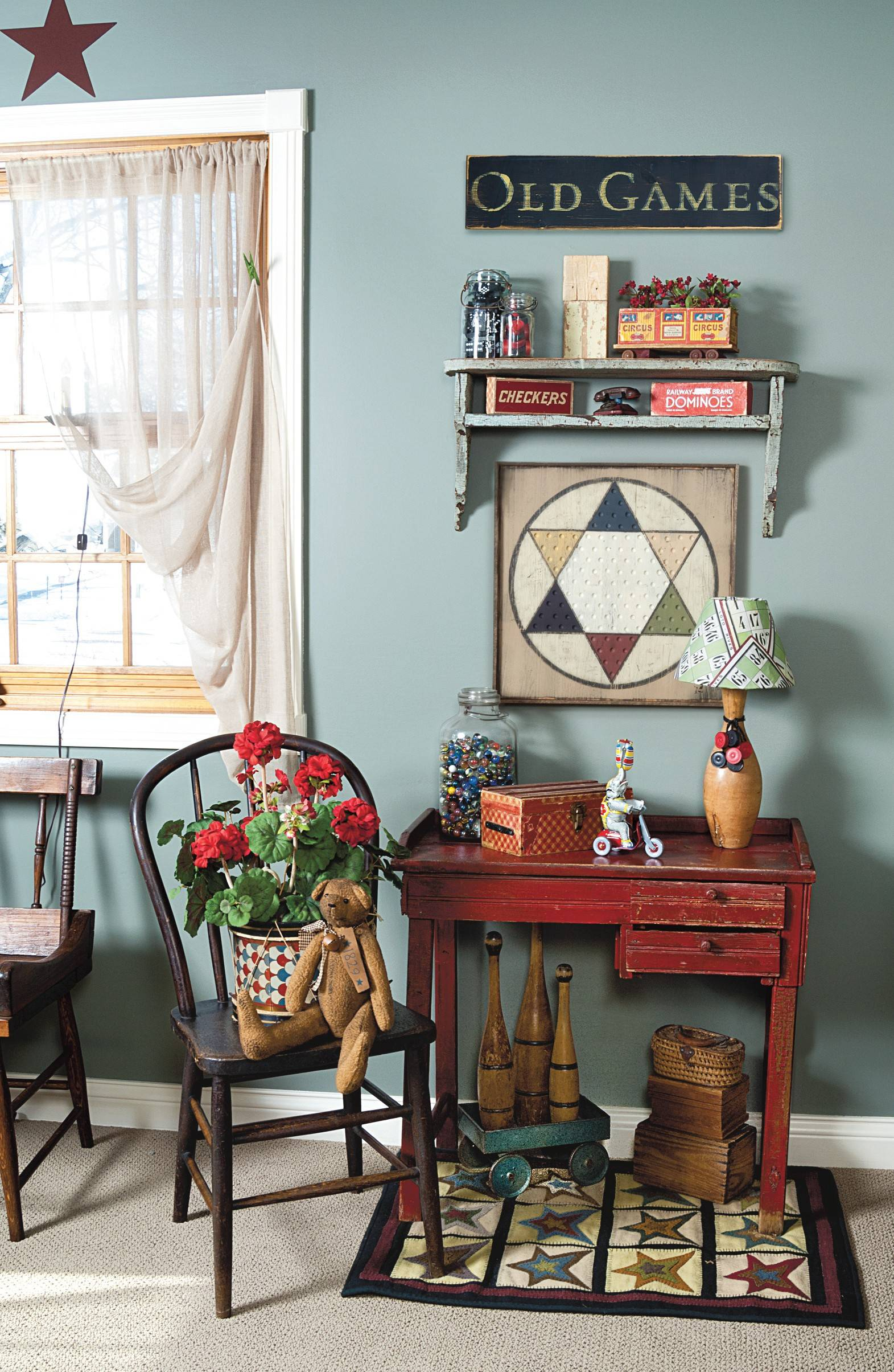 A well-aged red desk provides a splash of color against the blue-green wall and offers a vibrant contrast to the room's wood-toned furniture.