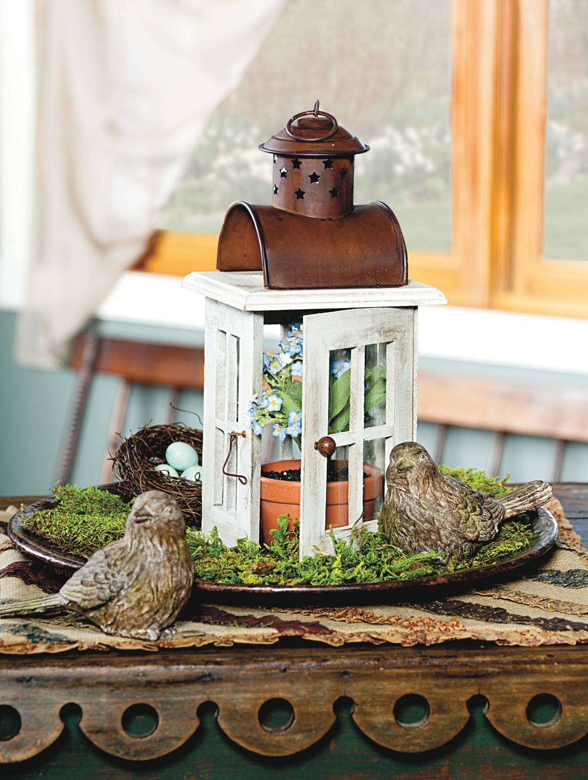Instead of using a lantern for its traditional purpose, take out its light source and replace it with a pretty potted plant. To give it more visual impact, rest it on a platter loaded with moss, and then add a few bird accents.