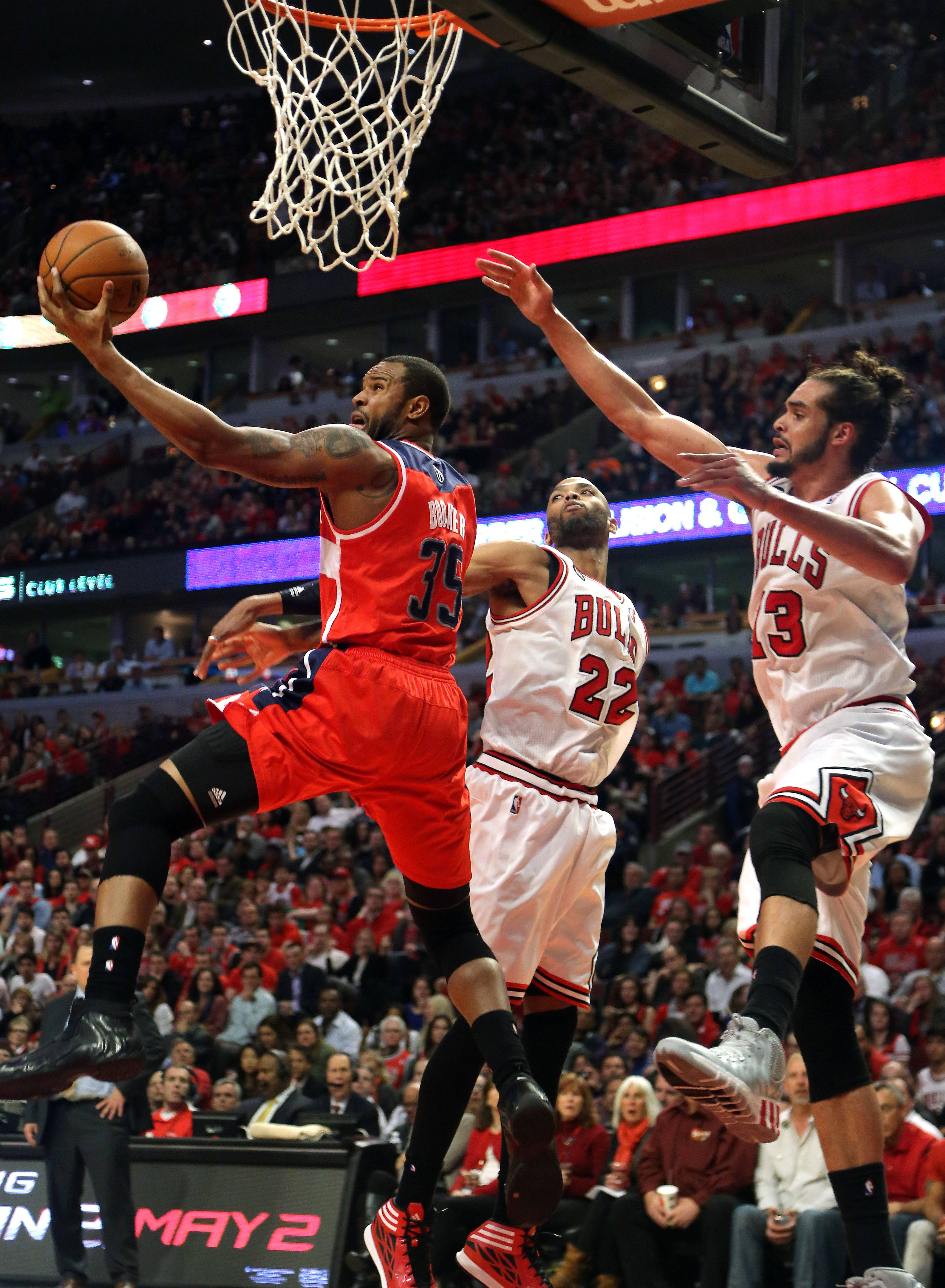 Washington Wizards forward Trevor Booker drives on Chicago Bulls forward Taj Gibson and Chicago Bulls center Joakim Noah.