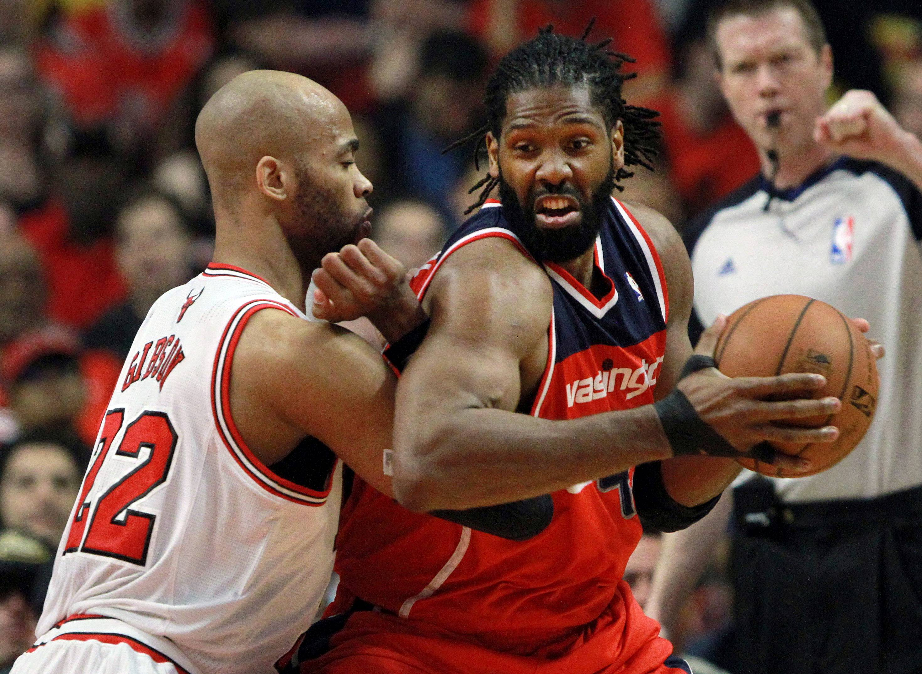 Washington Wizards forward Nene Hilario drives on Chicago Bulls Forward Taj Gibson.