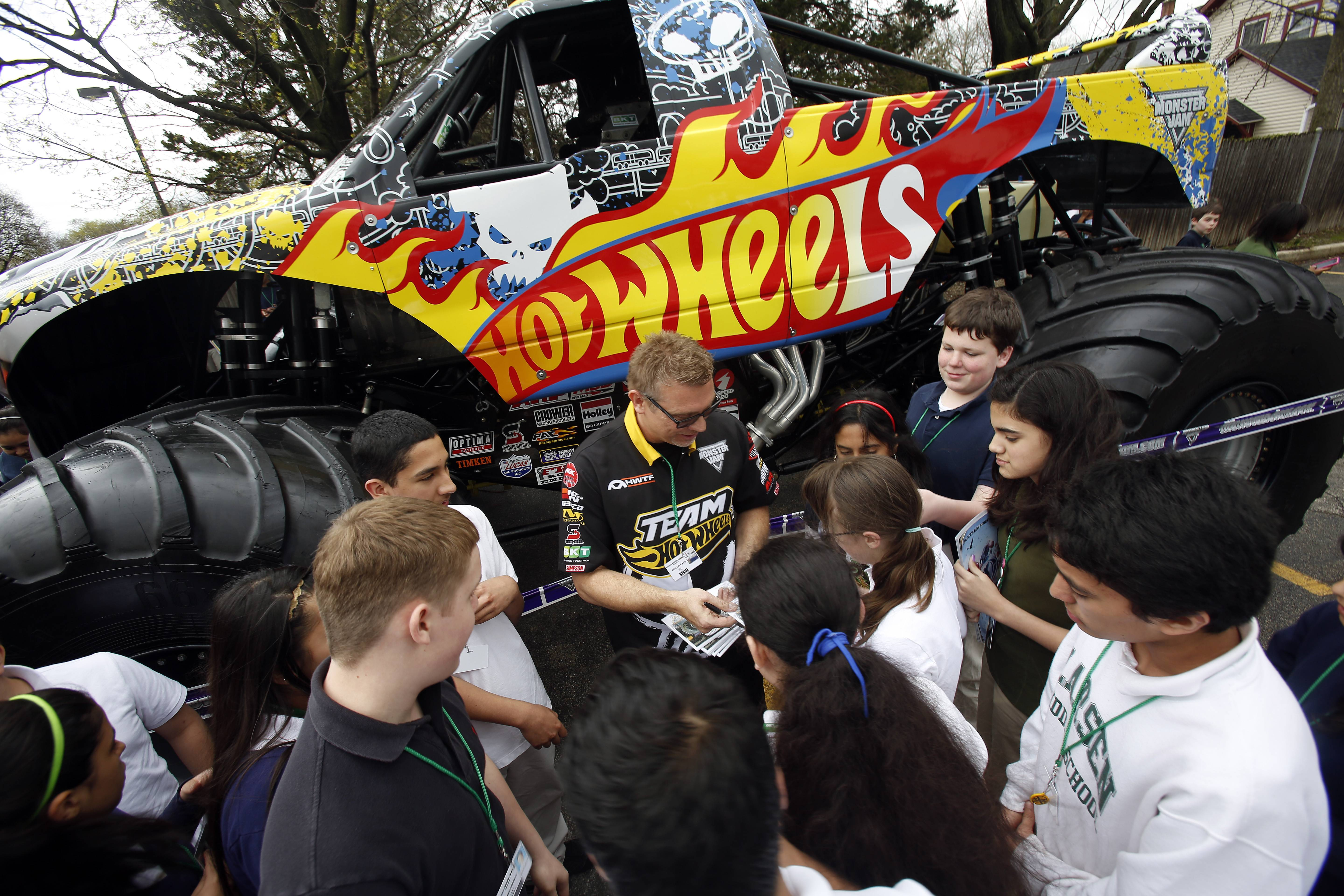 Larsen Middle School alumnus Scott Buetow, a driver for the Hot Wheels team on the Monster Jam circuit, signs autographs for students Tuesday at the Elgin school.