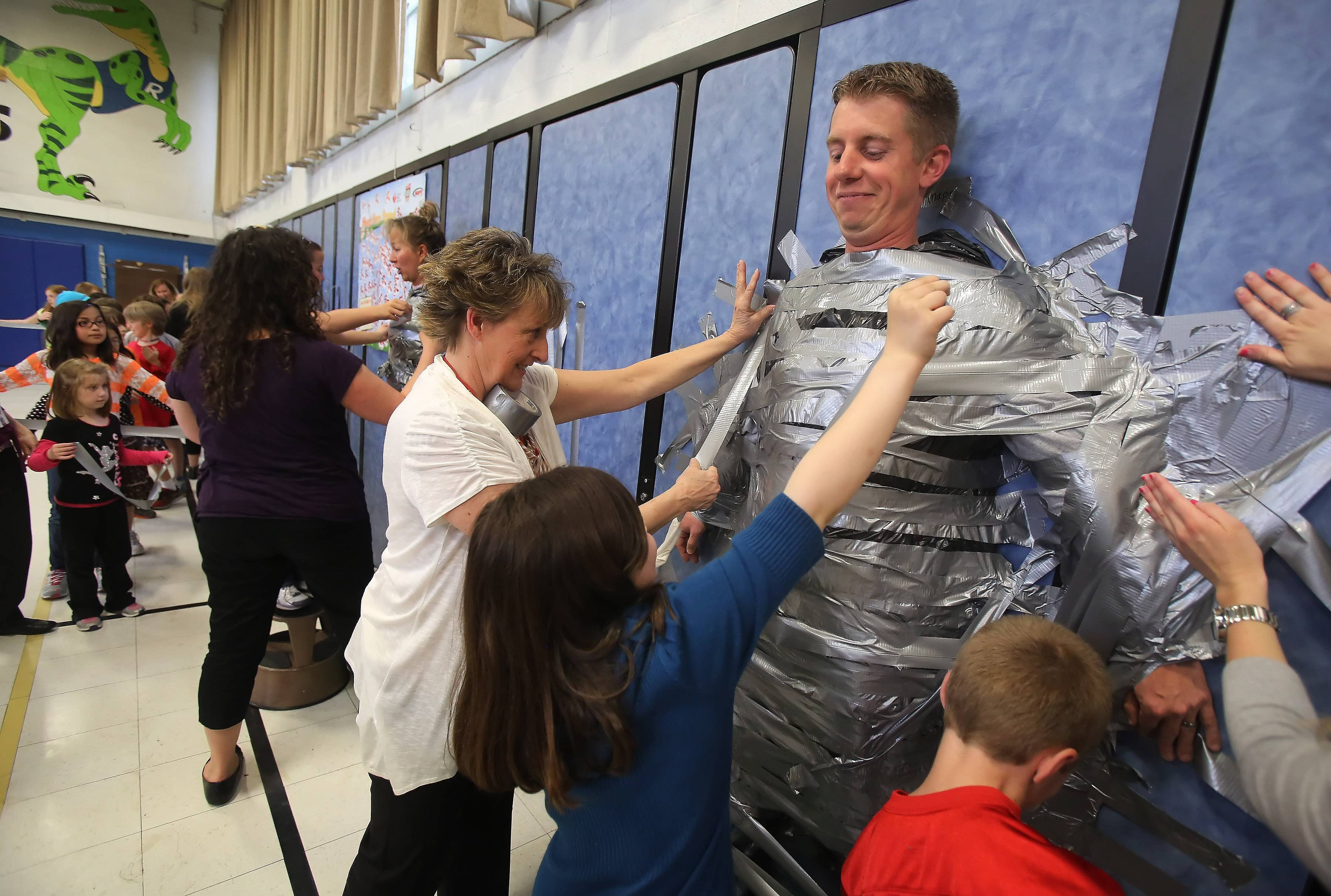 Rockland School students duct-tape Principal Jeff Knapp to the gym wall Tuesday to help celebrate the $7,217.46 raised for the American Heart Association through the Jump Rope For Heart at the Libertyville school. Learning Center Director Becky Johnson and physical education teacher Michael Kolar also were taped to the wall by students.