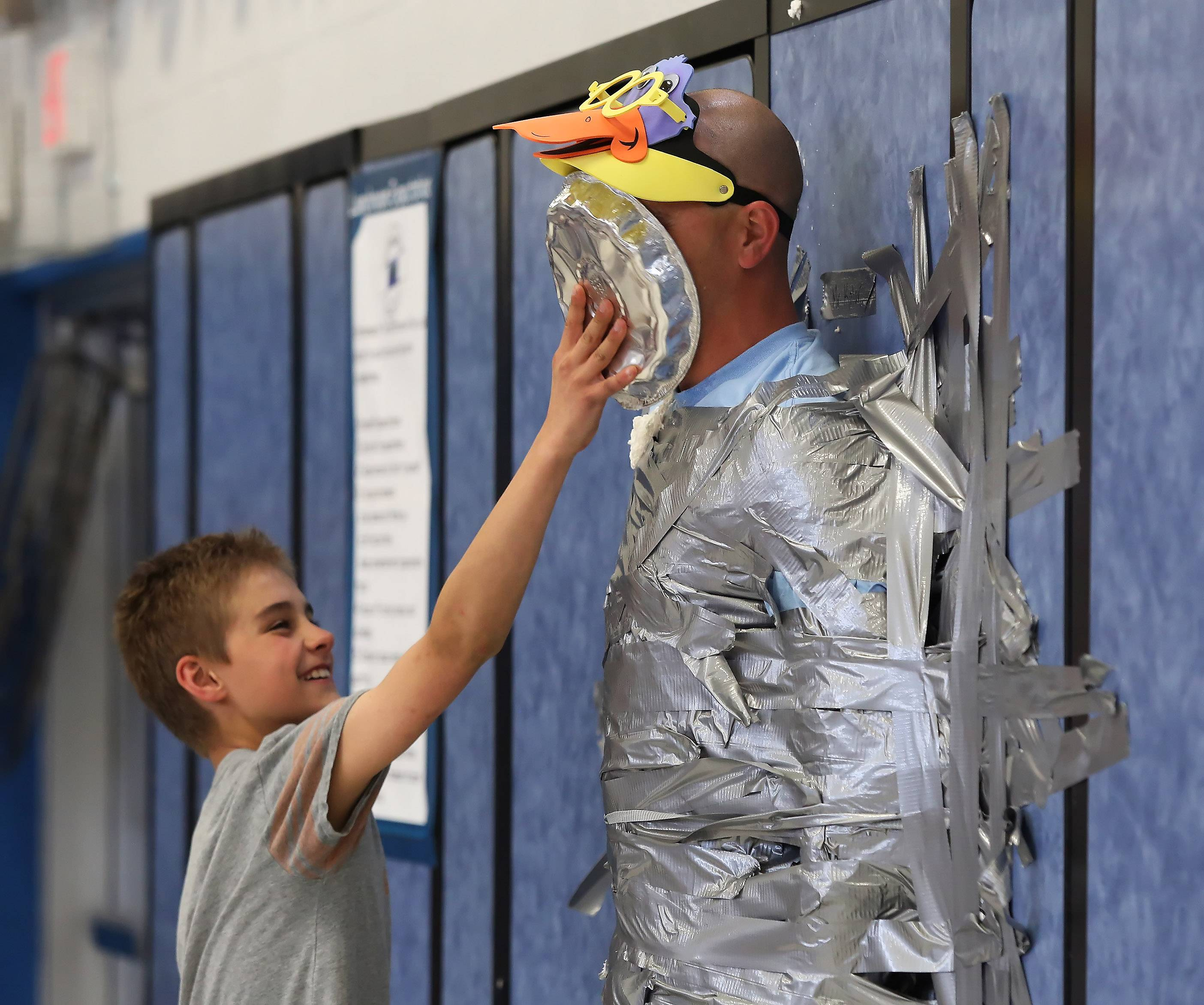 Rockland School fifth-grader Owen Elfering throws a pie in the face of physical education teacher Michael Kolar during an assembly Tuesday to celebrate the $7,217.46 raised for the American Heart Association through the Jump Rope For Heart fundraiser.