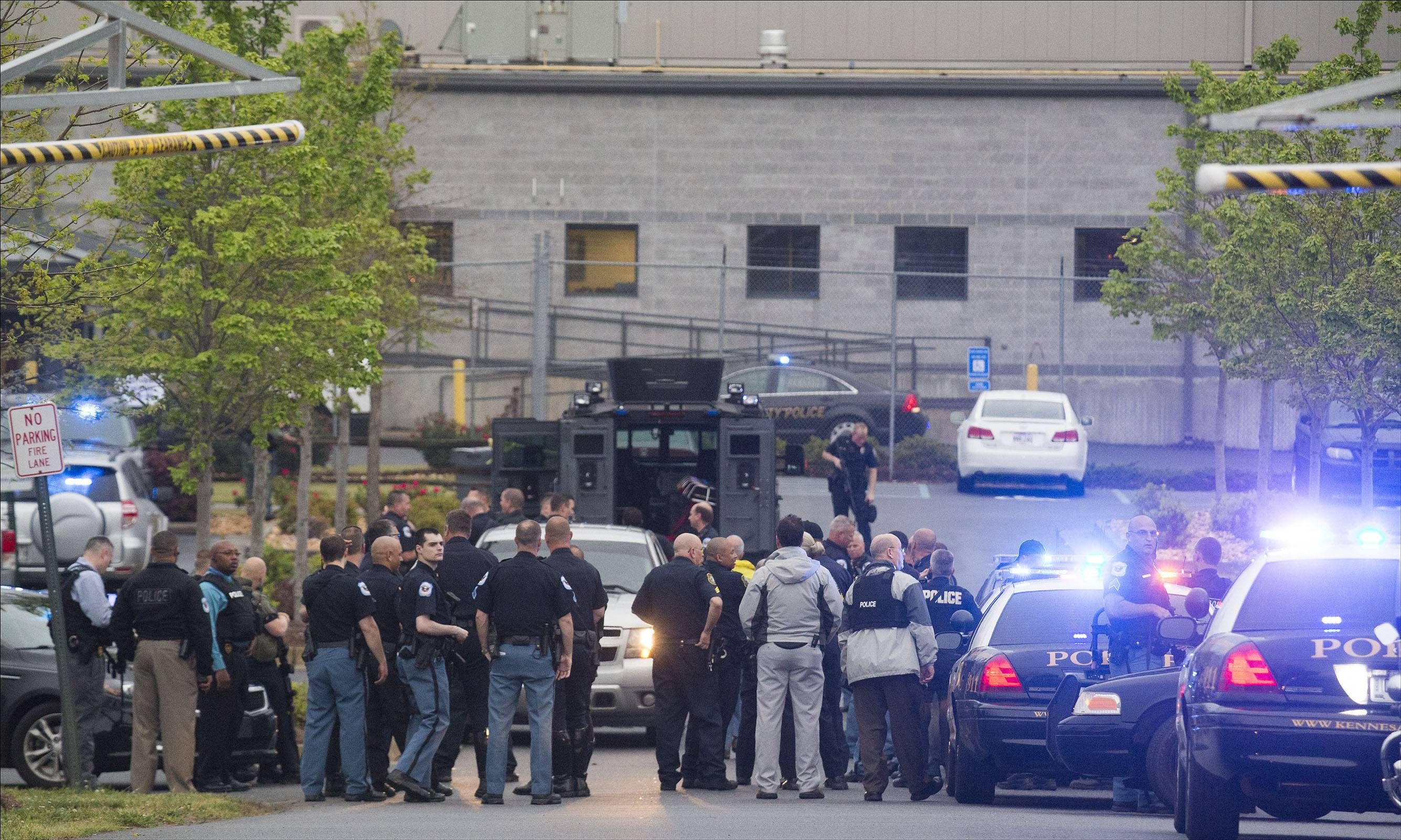 Police officers from Cobb County, Marietta and Kennesaw departments stage near the entrance of the Federal Express Ground building in Kennesaw, Ga., Tuesday after a man opened fire inside the building before turning the gun on himself.