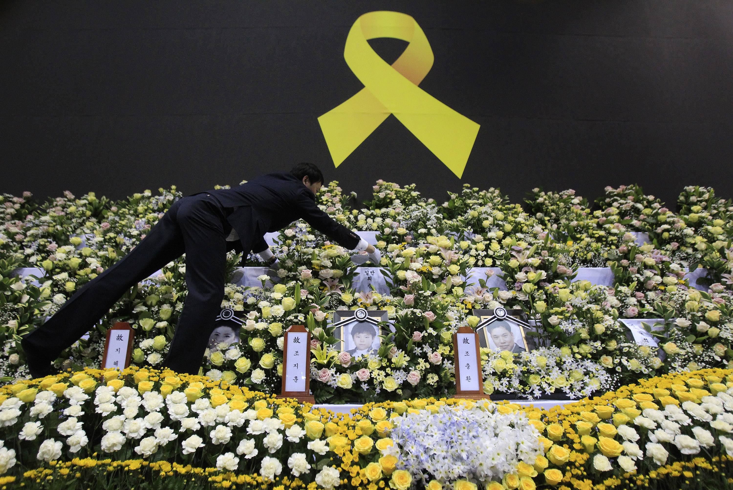 A funeral service employee sets up a group memorial altar Tuesday for victims of the sunken ferry. South Korean President Park Geun-hye apologized Tuesday for the government's inept initial response to a deadly ferry sinking as divers fought strong currents in their search for nearly 100 passengers still missing nearly two weeks after the accident.