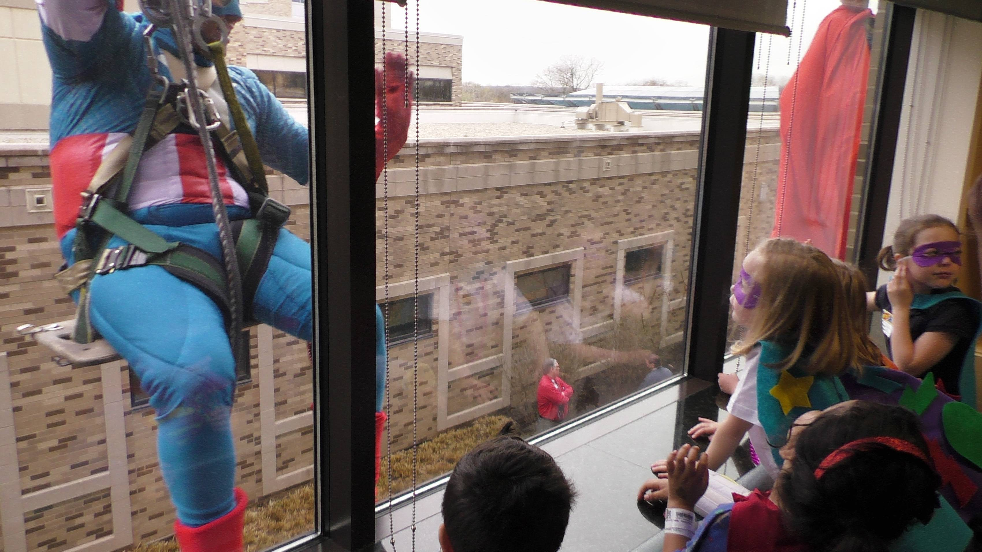 A window washer dressed as Captain America brings smiles to the face of past and current pediatric patients at Central DuPage Hospital Monday in celebration of National Superhero Day.