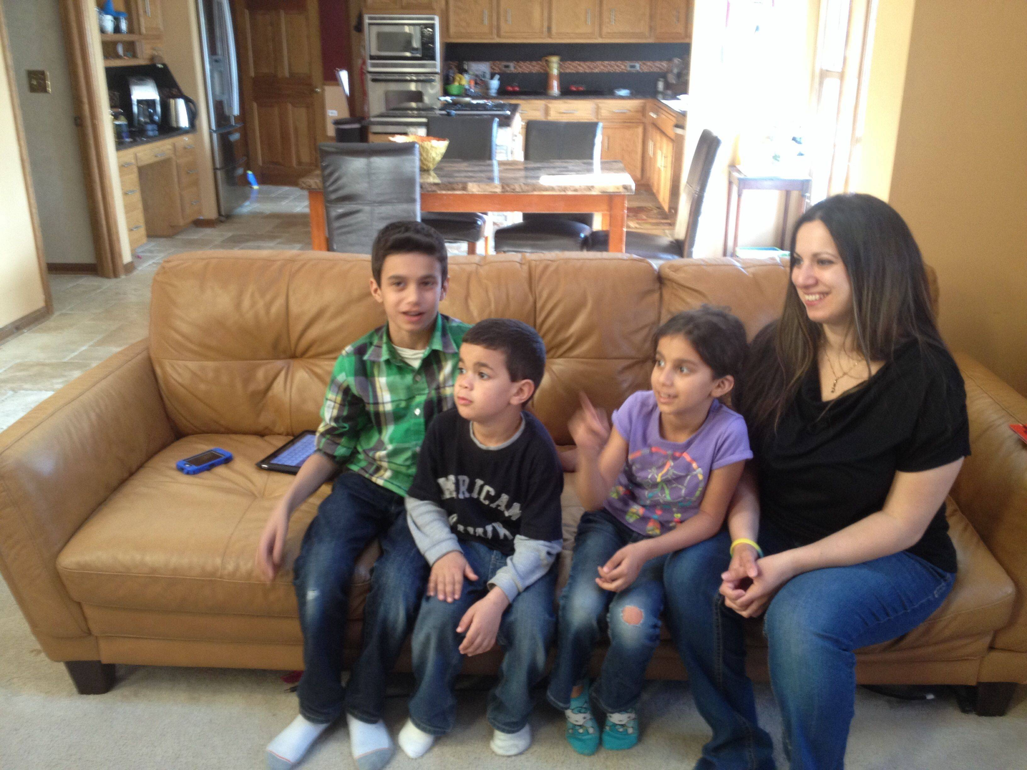"Just watching the new Muslim ""Happy"" video brings smiles to the faces of mom Angie Emara and her sons, Amir, left, and Aiman Mahmoud, and her daughter, Lara Mahmoud. The Naperville family are a part of the video designed to show the fun side of their lives as Muslims."