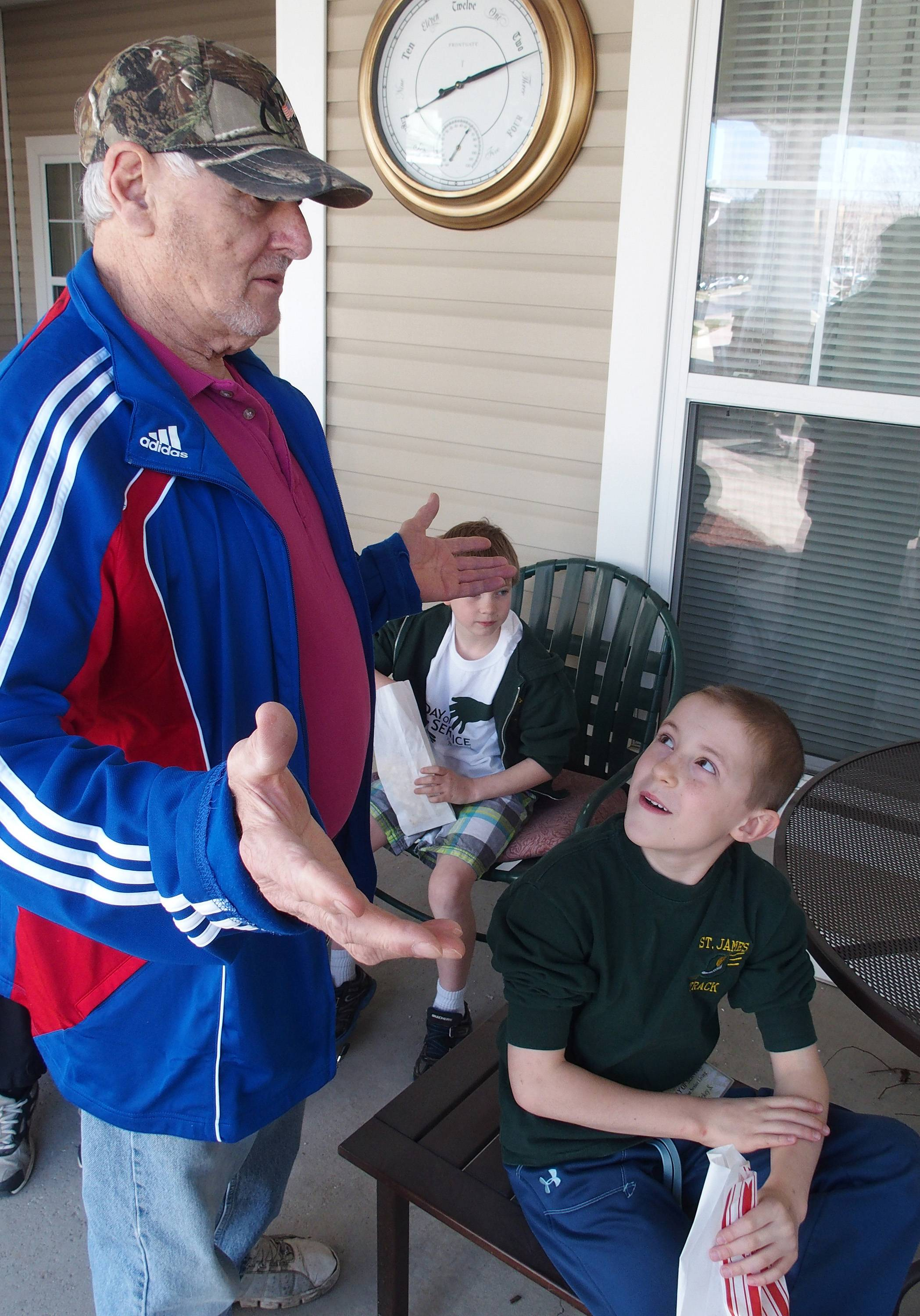Tony Shurba, a resident at Sunrise Senior Living Center and Brighton Gardens, passes out popcorn and chats with Mickey Schihl, a student from St. James the Apostle School, who was doing work at the center as part of a Day of Service project.