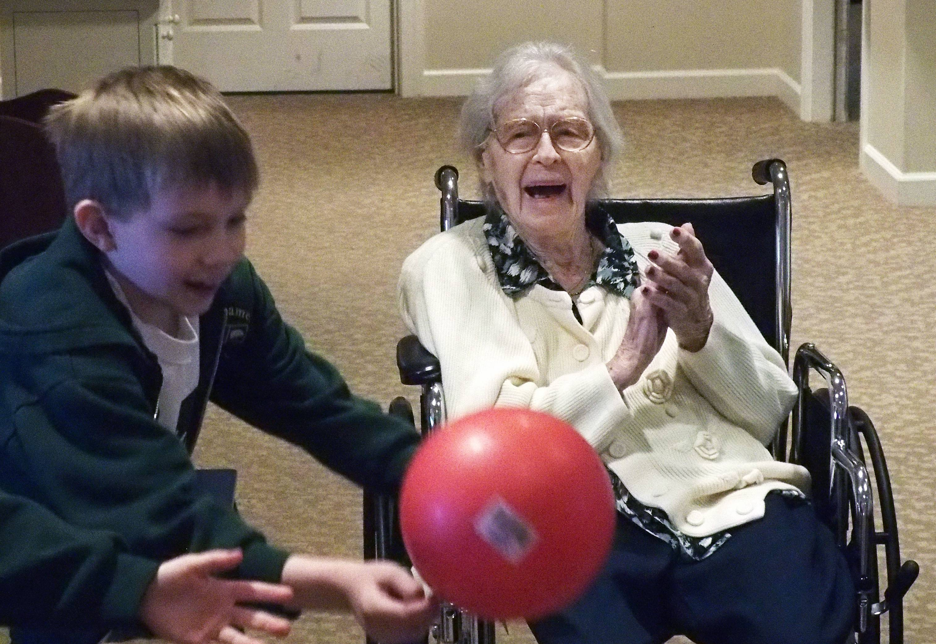 "Dorothy Michalaski, a resident of Sunrise Senior Living Center and Brighton Gardens in Glen Ellyn, plays in a ""chair"" volleyball game with students from St. James the Apostle School. The students spent a recent day applying what they've been learning in their religion classes by performing service projects in locations around town."