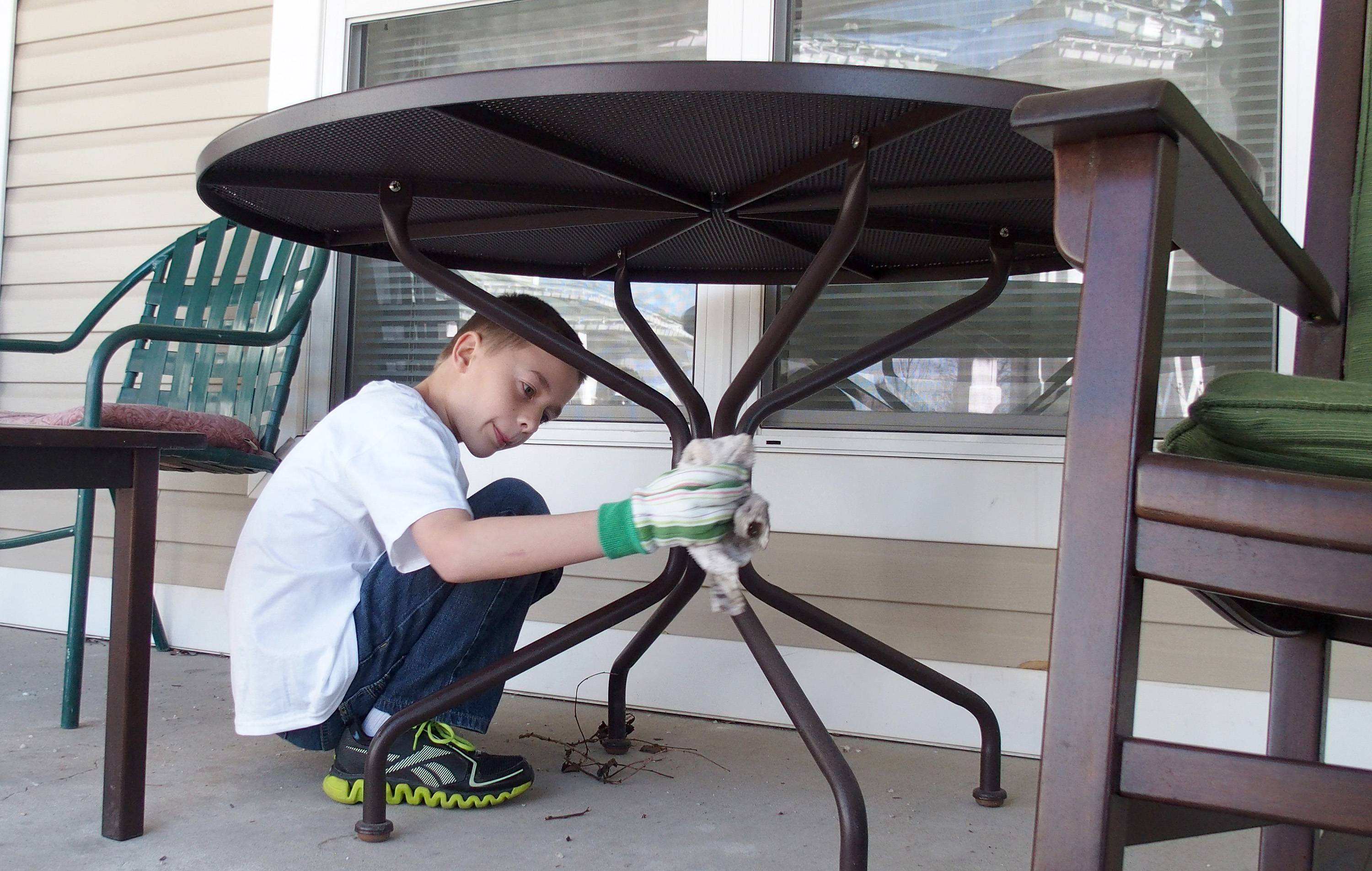 Kyle Prout, one of the students from St. James the Apostle School in Glen Ellyn, helps clean up outside tables and chairs at Sunrise Senior Living Center and Brighton Gardens.