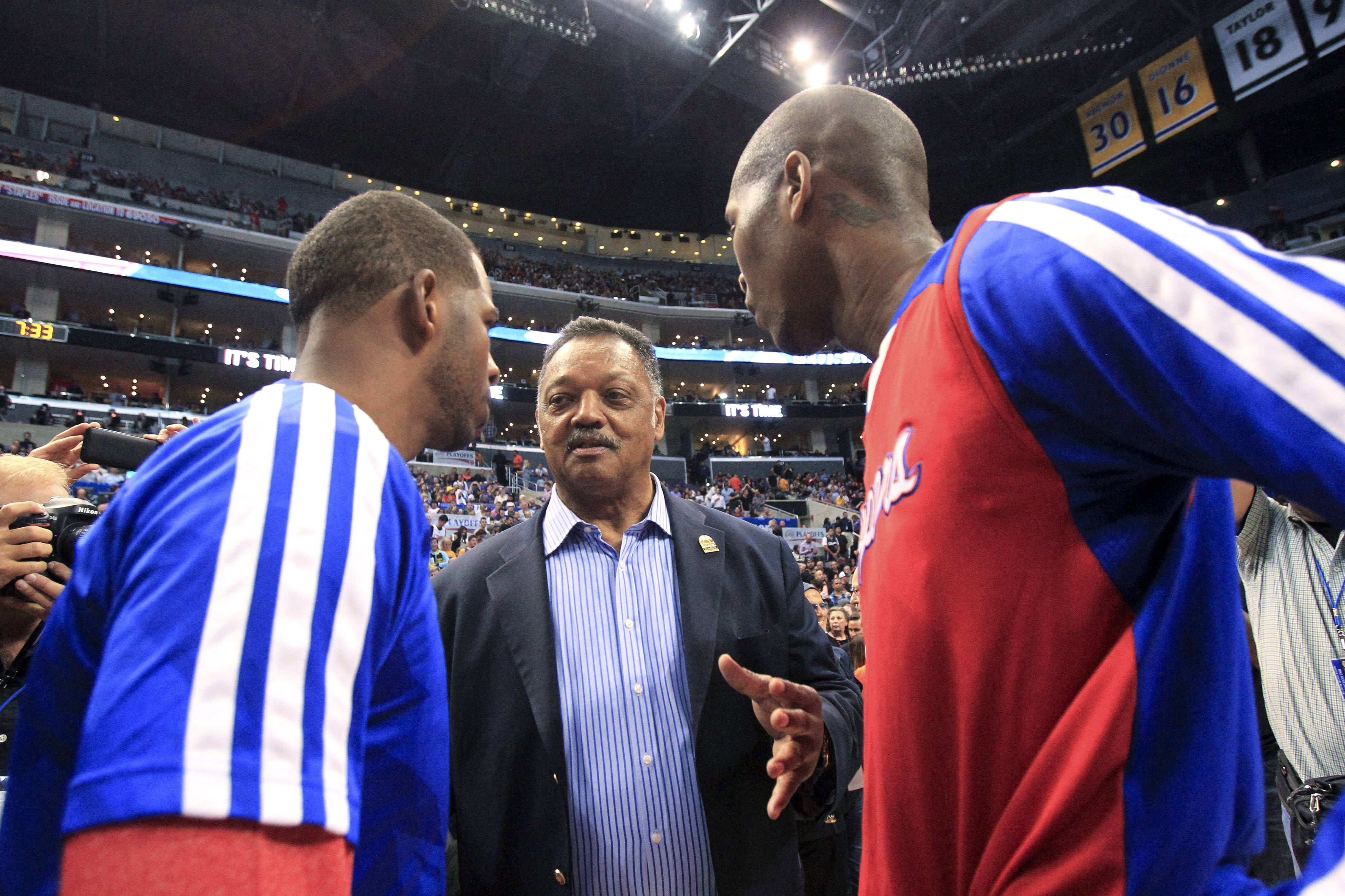 The Rev. Jesse Jackson, center, talks to Los Angeles Clippers' Chris Paul and Jamal Crawford before Game 5 of the Clippers' opening-round NBA basketball playoff series against the Golden State Warriors on Tuesday, April 29, 2014, in Los Angeles. NBA Commissioner Adam Silver announced Tuesday that Clippers owner Donald Sterling has been banned for life by the league.
