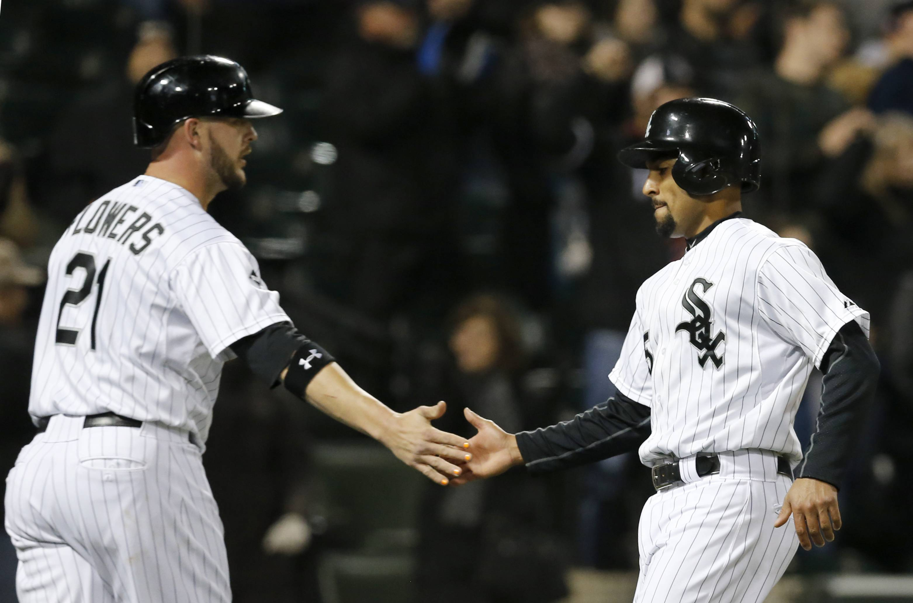 Chicago White Sox's Tyler Flowers, left, and Marcus Semien celebrate after scoring off a double by Adam Eaton, on a pitch by Tampa Bay Rays relief pitcher Jake McGee, during the sixth inning of a baseball game Monday in Chicago.