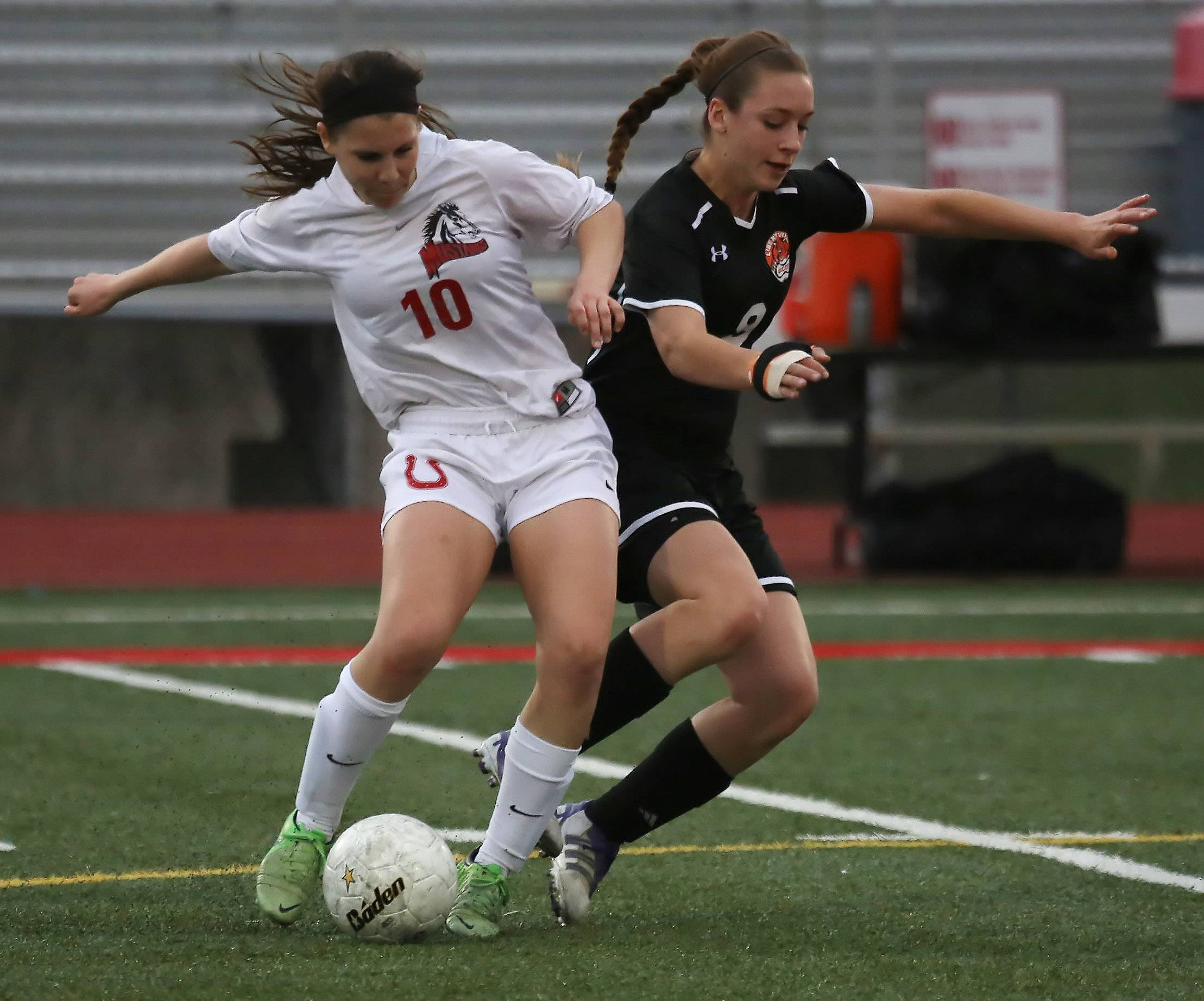 Mundelein's Kaila Cancelli (10) battles to take the ball away from Libertyville's Abbey Peters (9) on Tuesday at Mundelein.