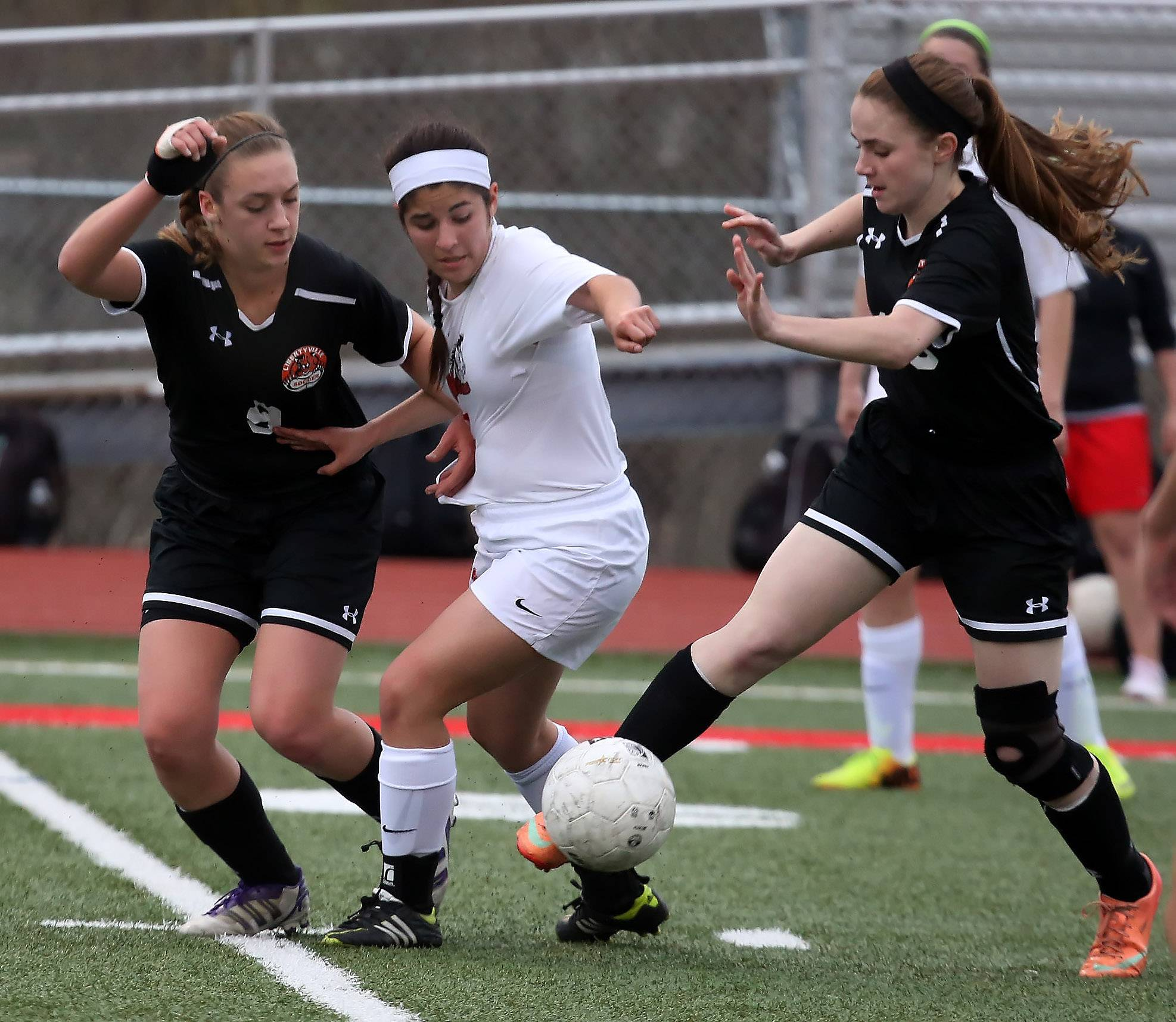 Libertyville defender Abbey Peters, left, pressures Mundelein midfielder Adriana Salse with help from midfielder Danielle Pacholski on Tuesday at Mundelein.