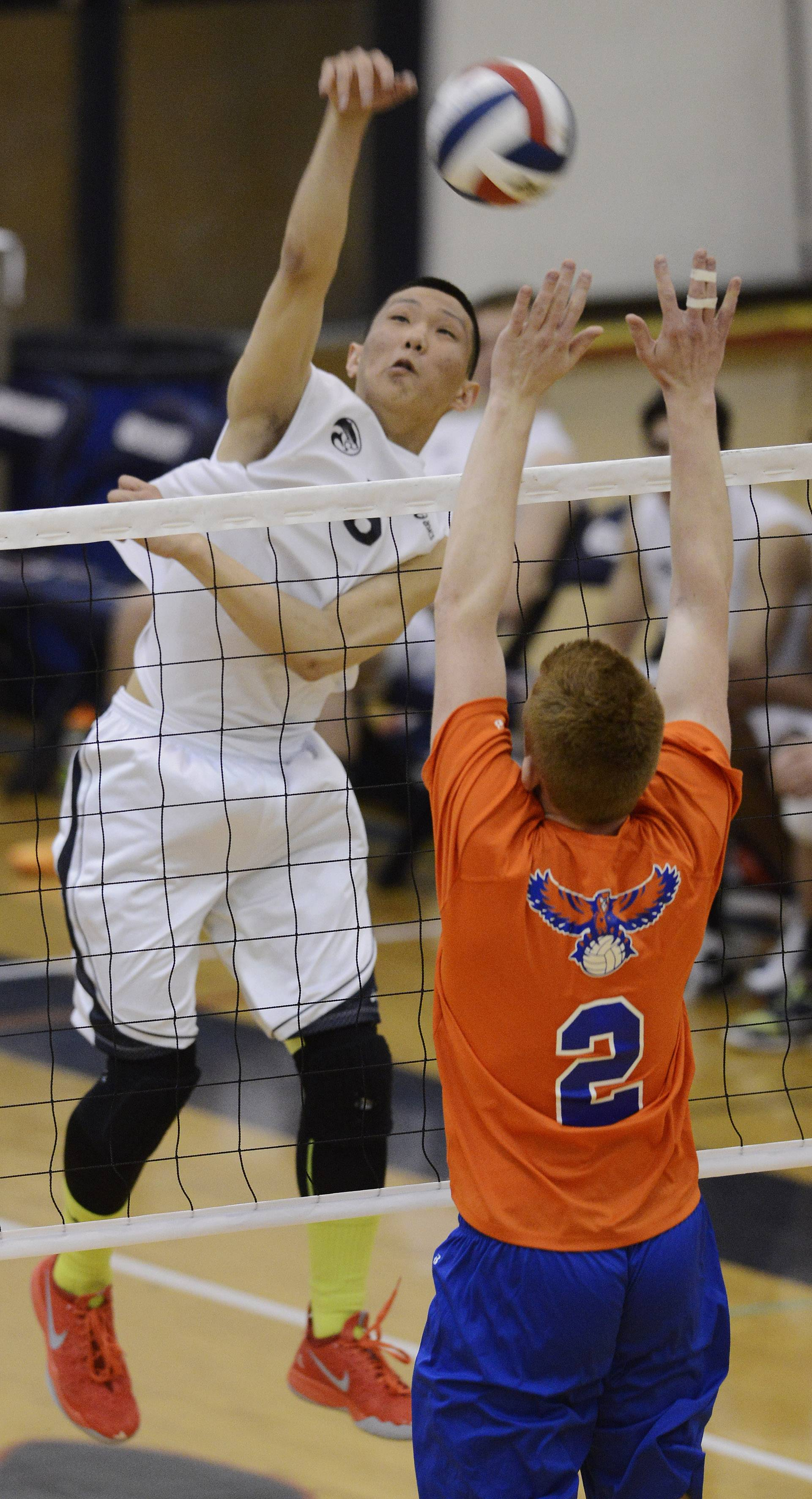 Conant's Jae Pyun leaps for a kill as Hoffman Estates' Piotr Wrobel tries to block the ball at the net during Tuesday's match.