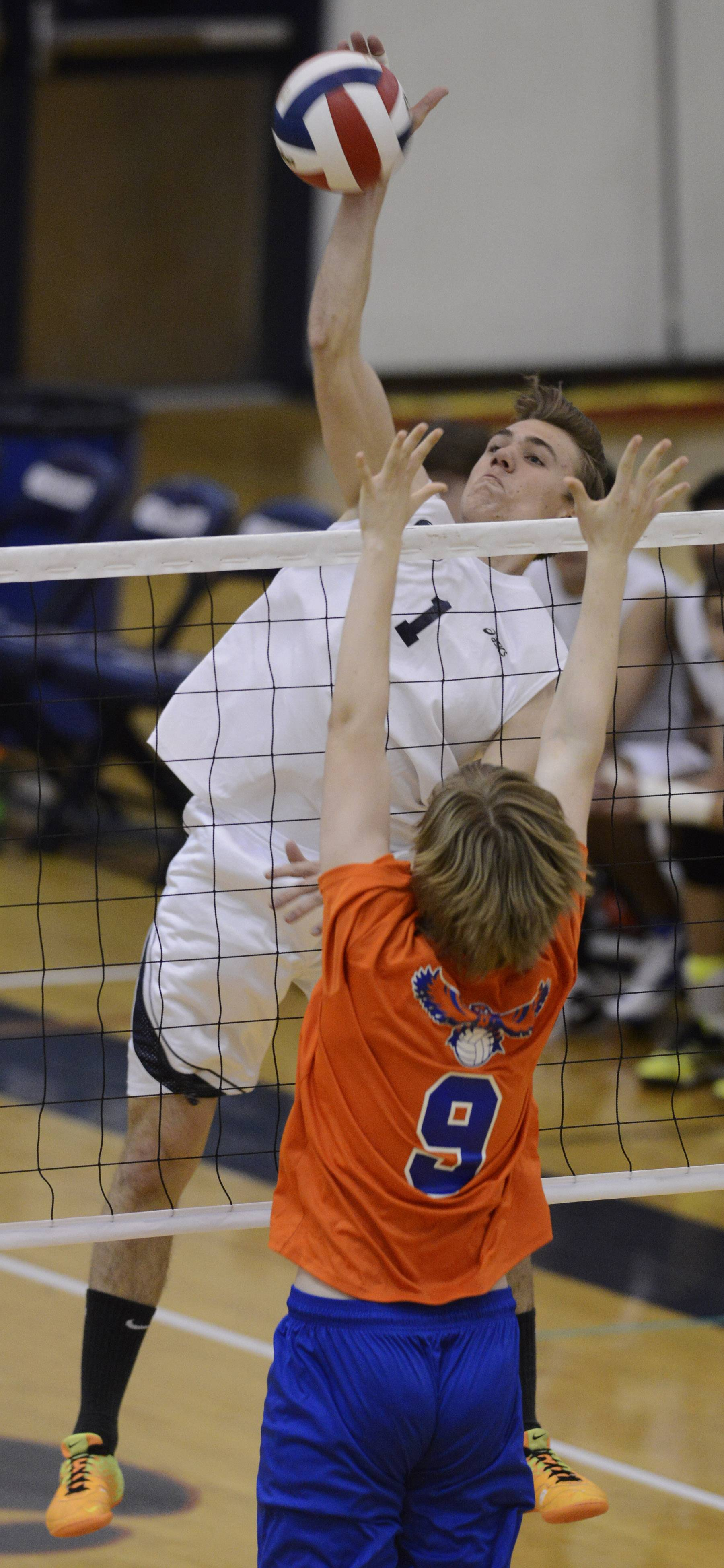 Conant's Patryk Openchowski leaps for a kill as Hoffman Estates' Hordan Ehlers tries to block the ball at the net during Tuesday's match.