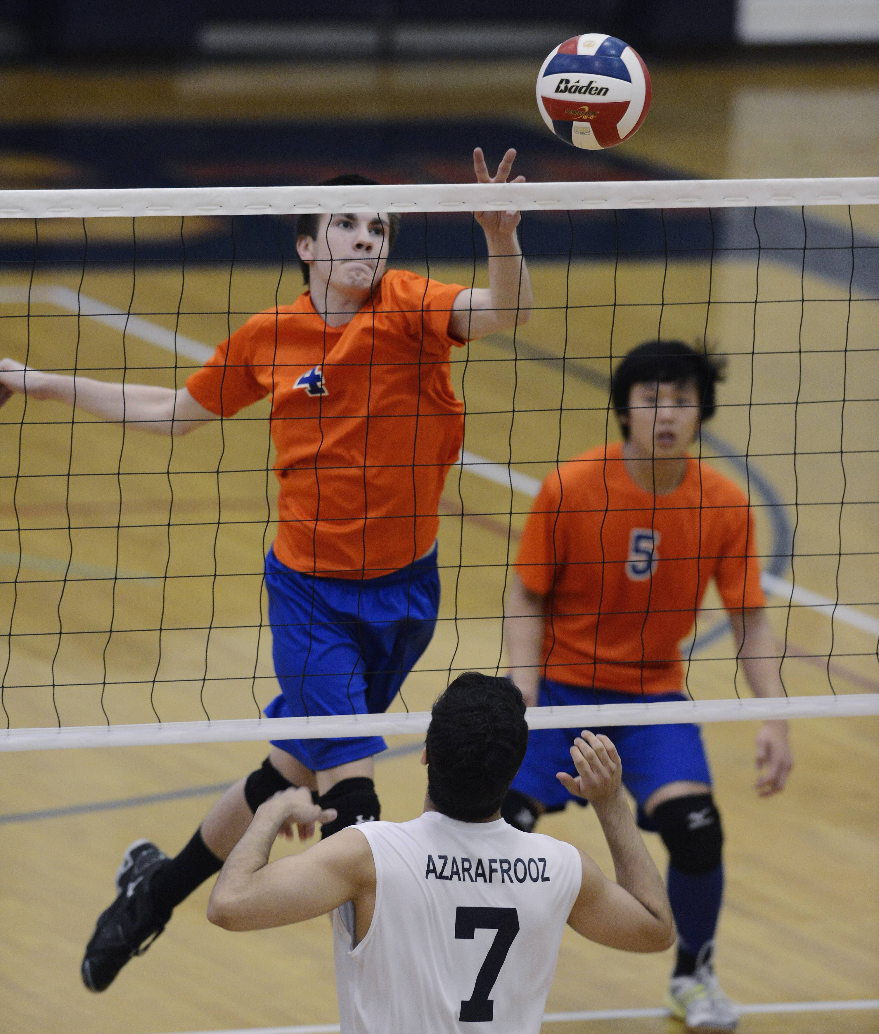 Hoffman Estates' Matt Stacy, left, taps the ball past Conant's Nickan Azarafrooz during Tuesday's match.