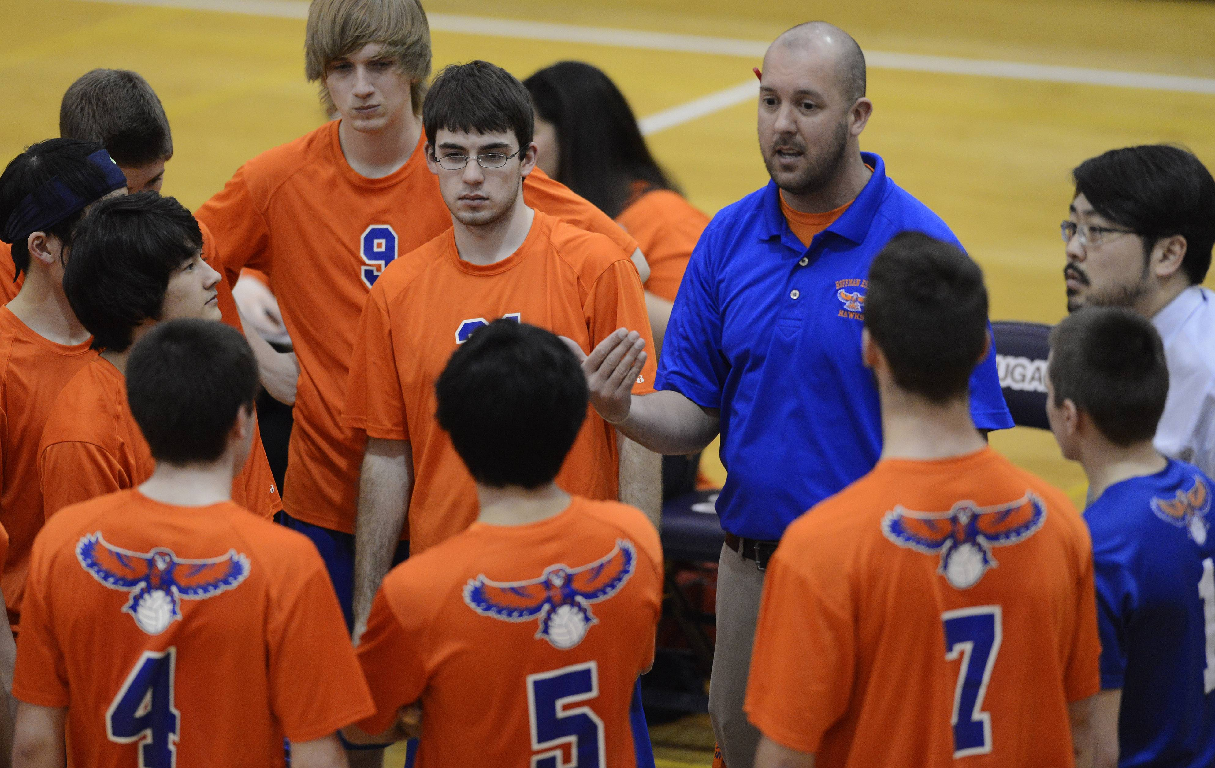 Hoffman Estates volleyball coach Dan Hutton talks with his team during a timeout.