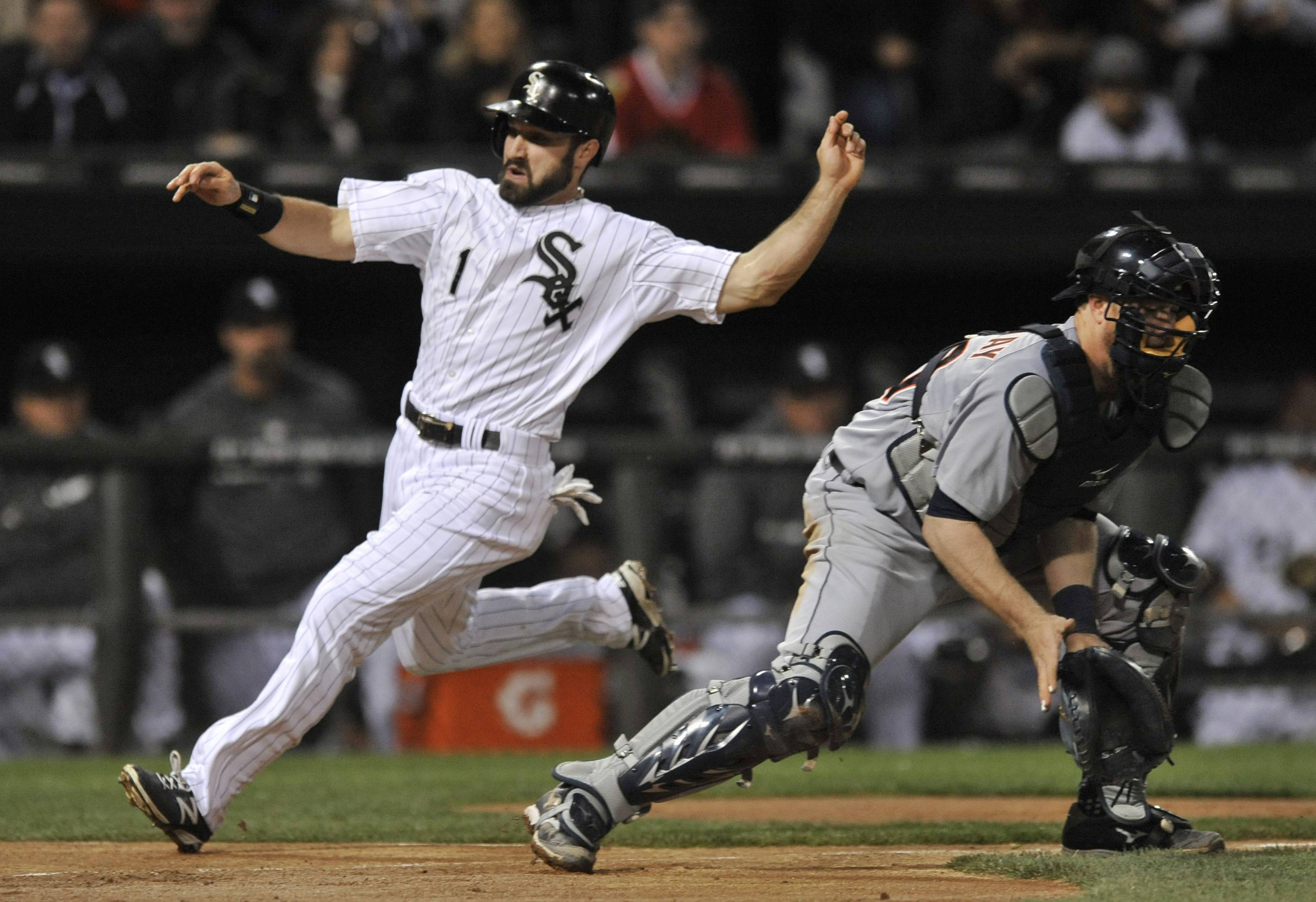 Chicago White Sox's Adam Eaton (1), crosses home plate safely as Detroit Tigers catcher Bryan Holaday waits for the throw during the third inning of a baseball game Tuesday in Chicago.