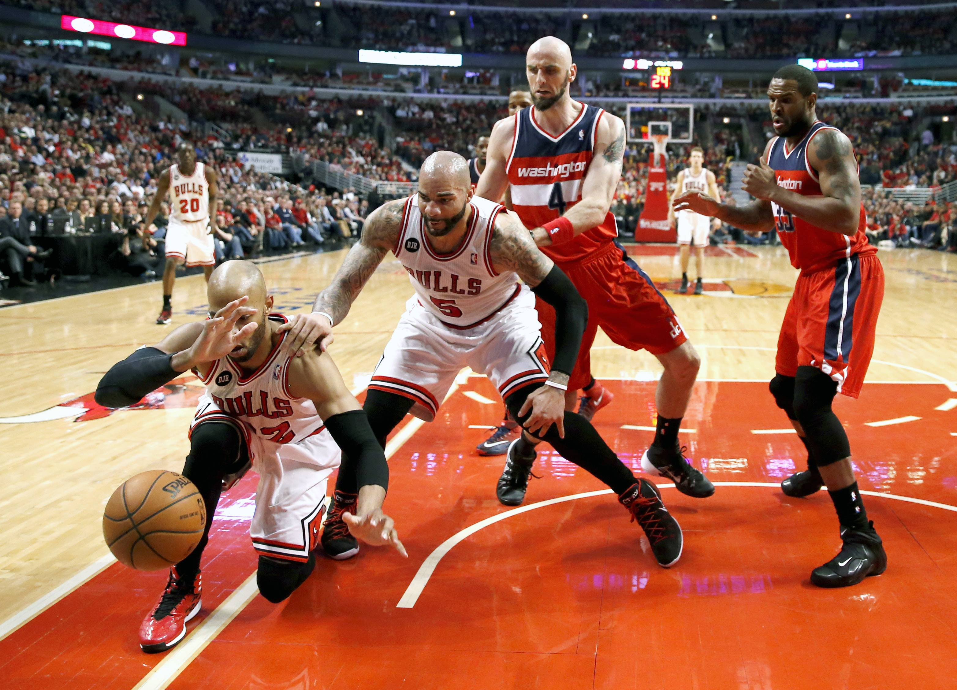 Chicago Bulls forward Taj Gibson (22) keeps the ball from going out of bounds as Carlos Boozer (5), Washington Wizards center Marcin Gortat (4) and Trevor Booker (35) stand near during the first half of Game 5 in an opening-round NBA basketball playoff series Tuesday in Chicago. The Bulls were eliminated from the playoffs with a 75-69 loss.